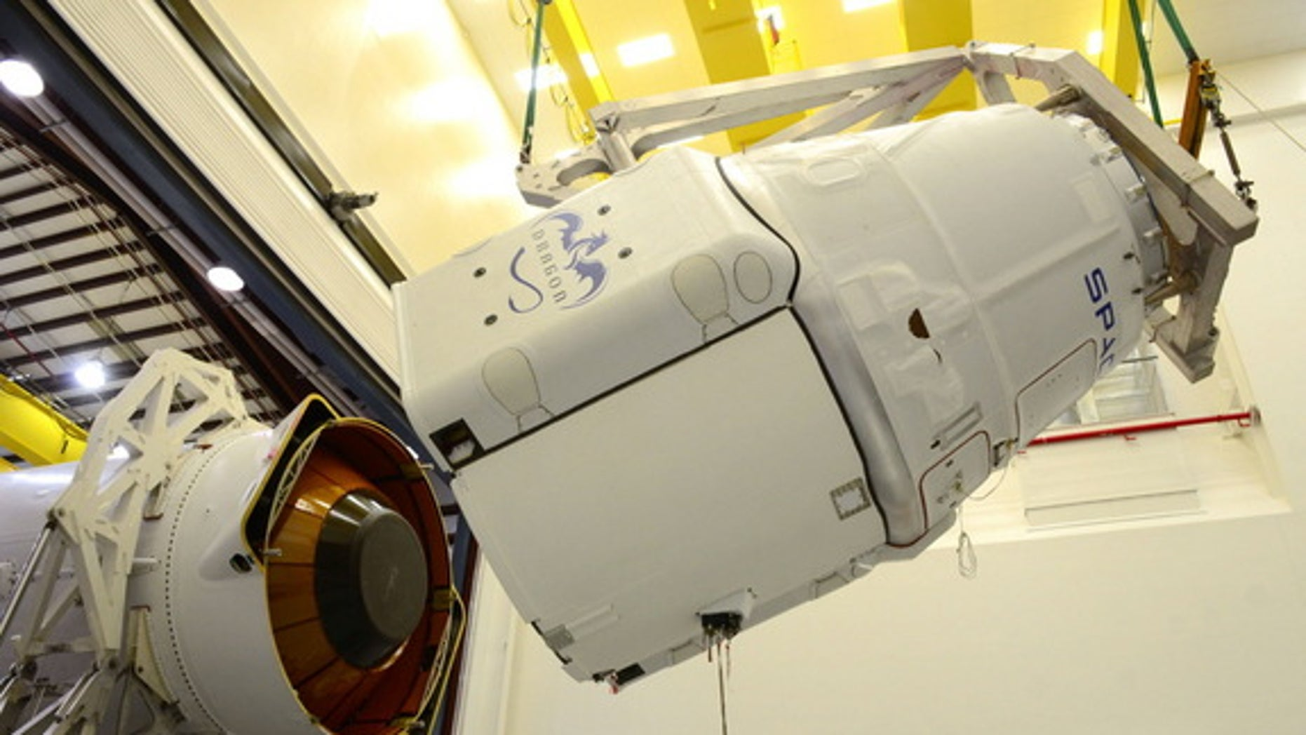 A SpaceX robotic Dragon space capsule is mated to the top of its Falcon 9 rocket ahead of a planned March 2014 launch to the International Space Station from Cape Canaveral Air Force Station, Florida. Image released March 11.