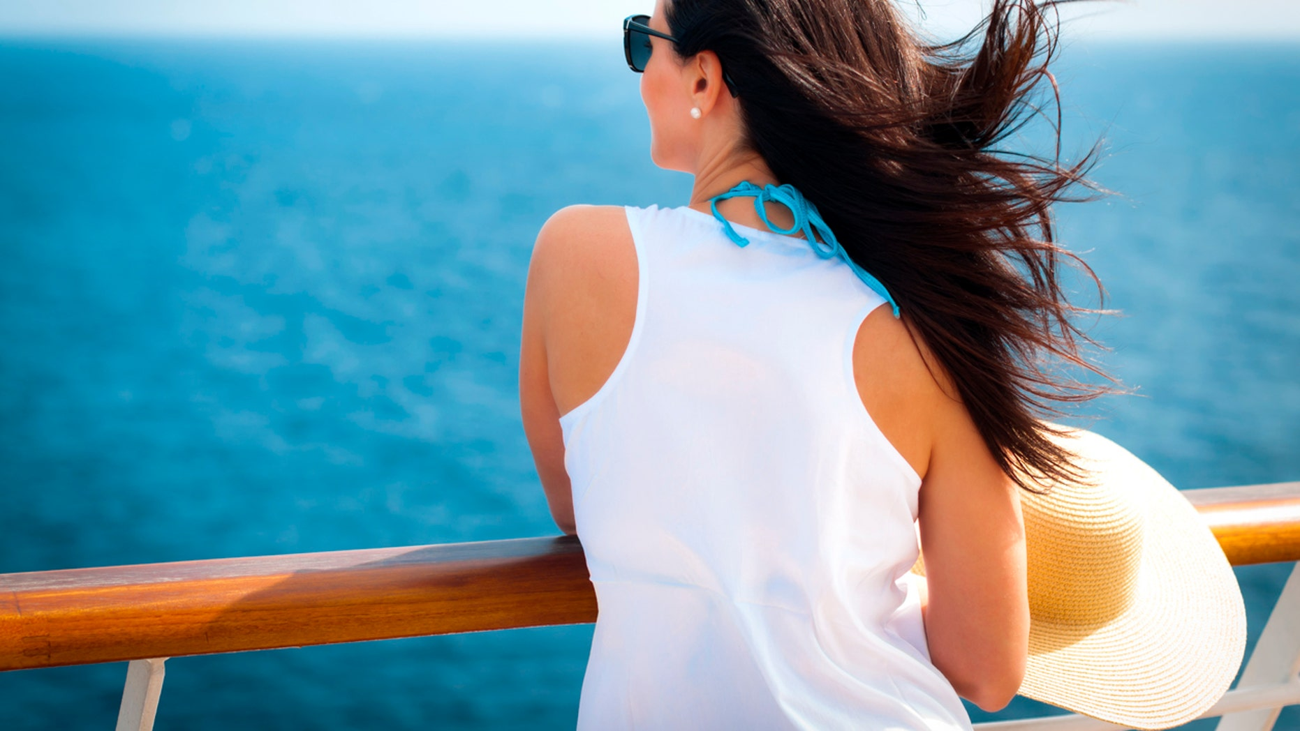 Woman wearing a floppy straw hat and a white dress standing next to the railing on a cruise ship