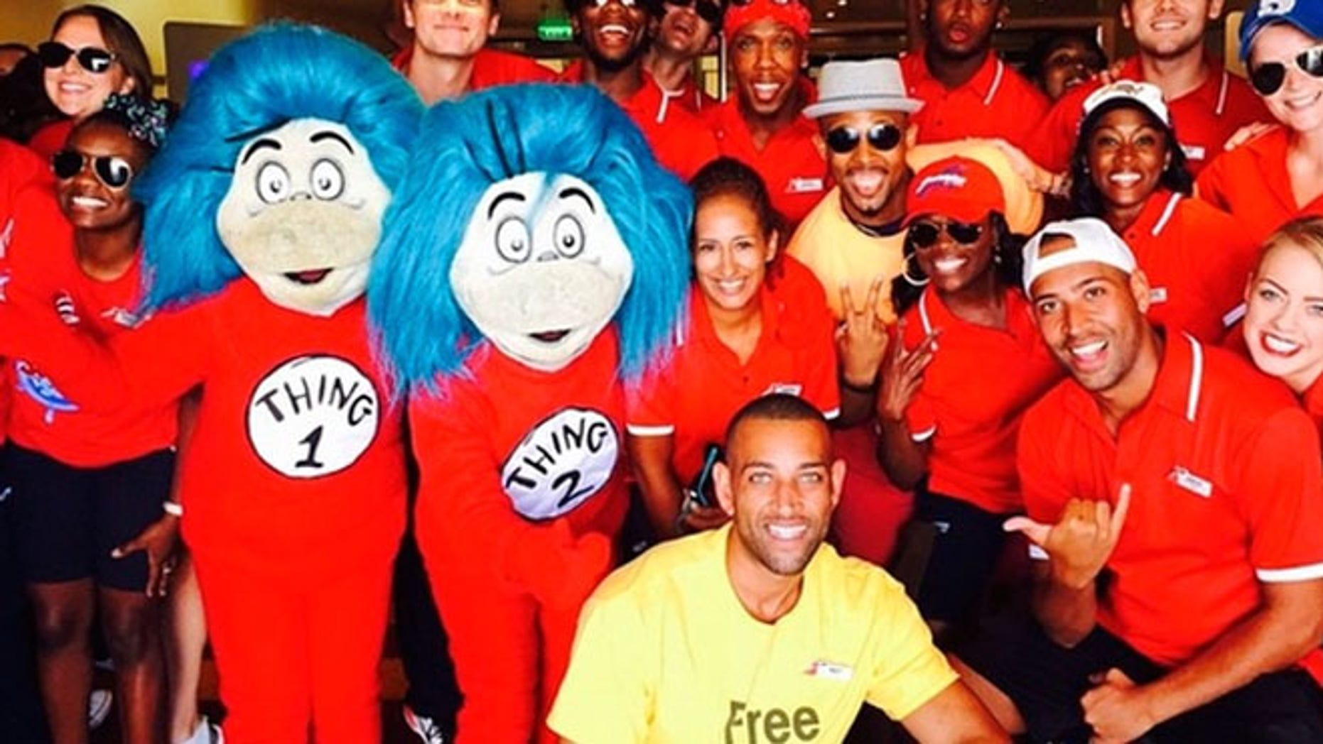 """Carnival Breeze cruise director Matt Mitcham (in the yellow """"Free Hugs"""" shirt) with his entertainment staff and a couple of special guests."""