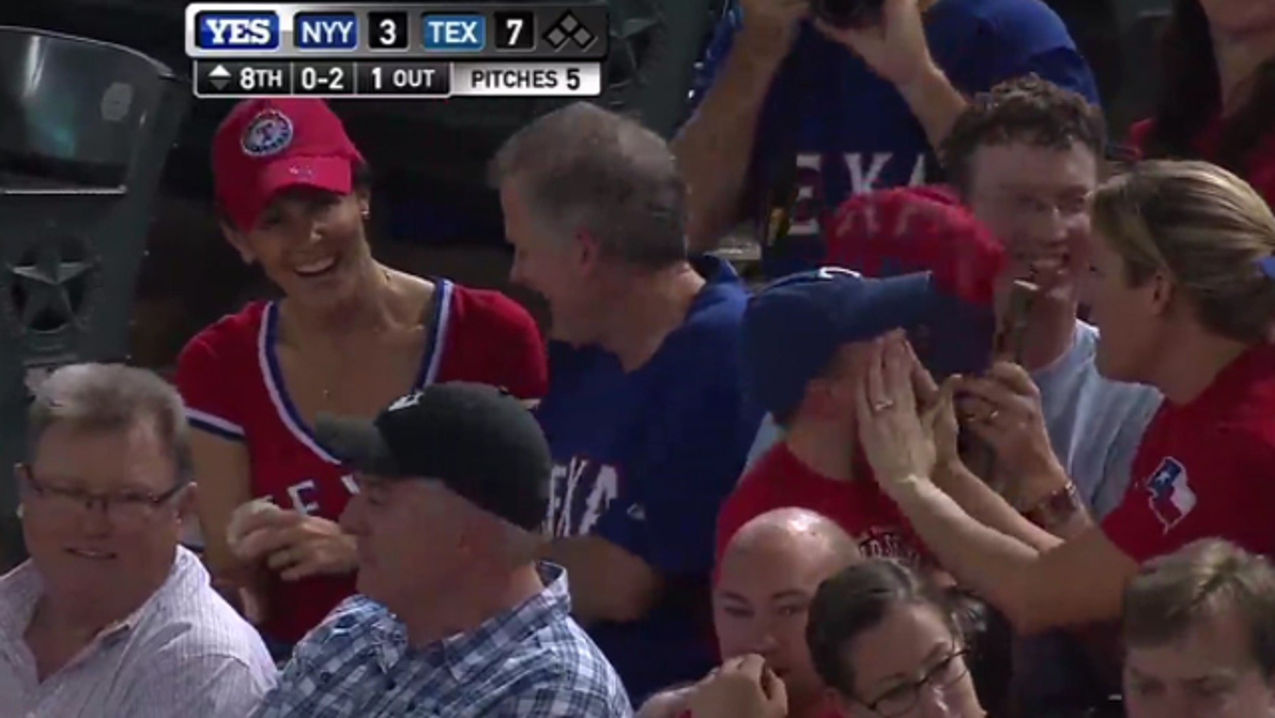 Shannon Moore, far left, and Sean Leonard celebrate catching a ball tossed into the stands during Wednesday's Rangers-Yankees game as 3-year-old Cameron Shores cries.