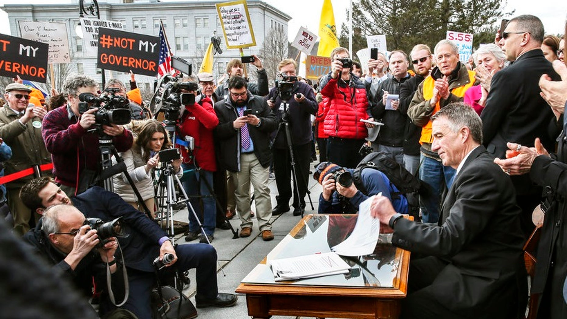"""Facing signs that read """"Not my governor"""" and amid taunts and jeers, Vermont GOP Gov. Phil Scott signed into law the state's first-ever sweeping gun control measures."""