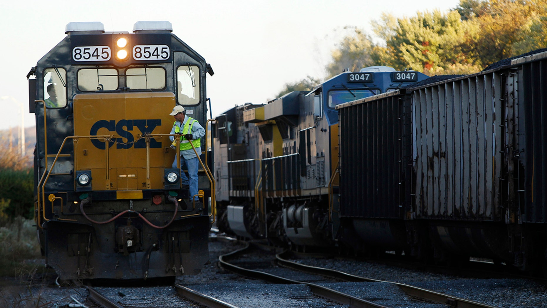 A CSX coal train, right, moves past an idling CSX engine at the switchyard in Brunswick, Md., Oct. 16, 2012.
