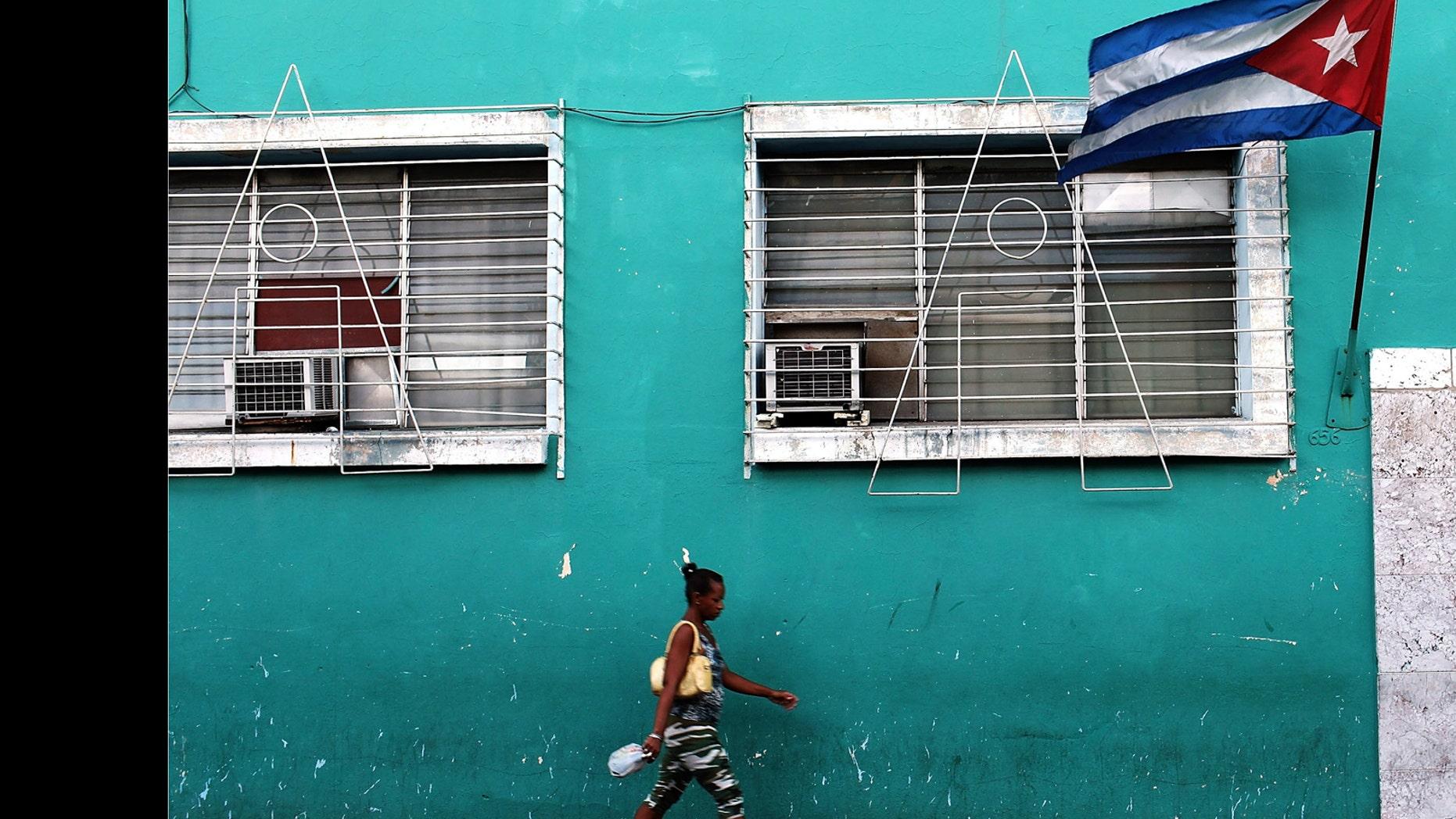 A woman walks under a Cuban flag in Santiago de Cuba.