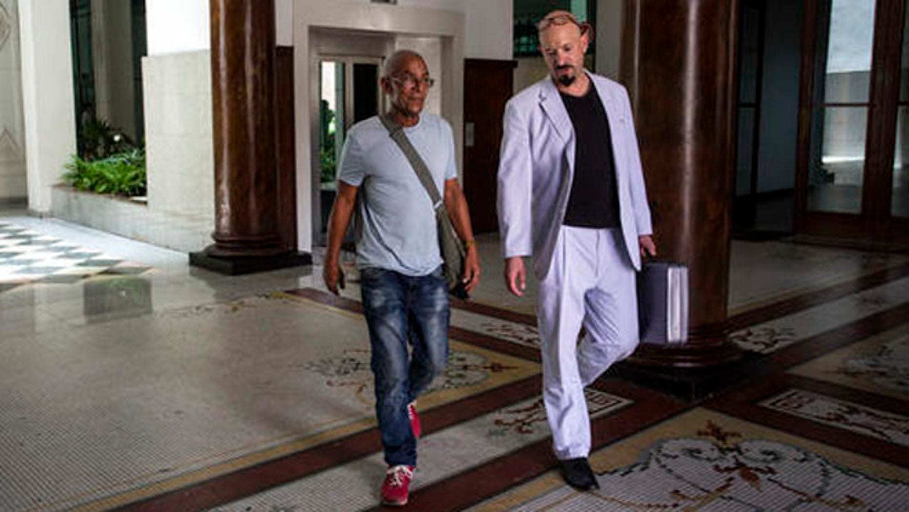 U.S. fugitive Charles Hill, left, walks with his lawyer Jason Flores Williams after an interview in Havana, Cuba, Friday, June 10, 2016. Hill, 66, who is sought in the 1971 killing of a New Mexico state policeman, told The Associated Press that Cuban contacts recently assured him he was at no risk of extradition. (AP Photo/Desmond Boylan)
