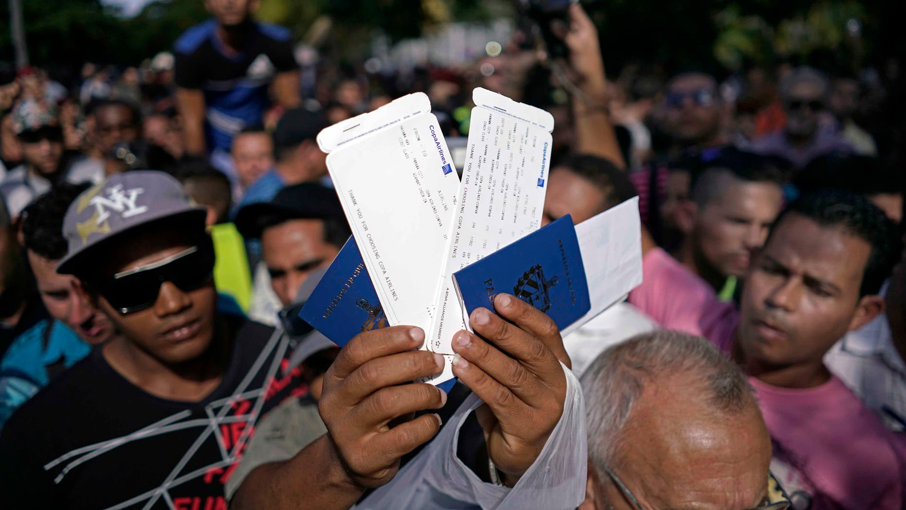 A man holds up airline tickets with destination to Ecuador, outside the Ecuadorian embassy, in Havana, Nov. 27, 2015.