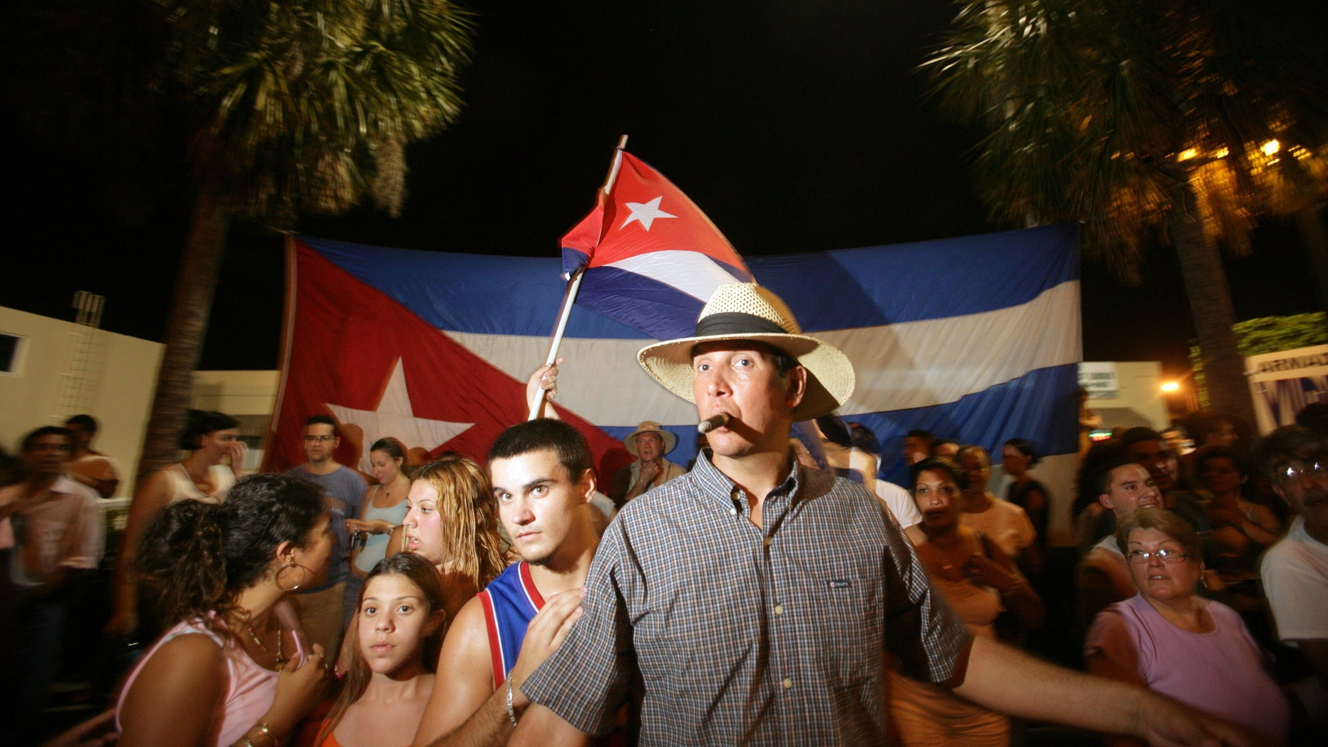 MIAMI - JULY 31: A crowd of Cubans wave flags and dance in the street after hearing news that Cuban leader Fidel Castro was ill and ceded power to his younger brother on July 31, 2006 in the Little Havana neighborhood of Miami, Florida. According to reports, Fidel Castro has temporarily handed over his Presidential powers to his brother Raul Castro and announced that he underwent surgery for intestinal bleeding.  (Photo by Richard Patterson/Getty Images)