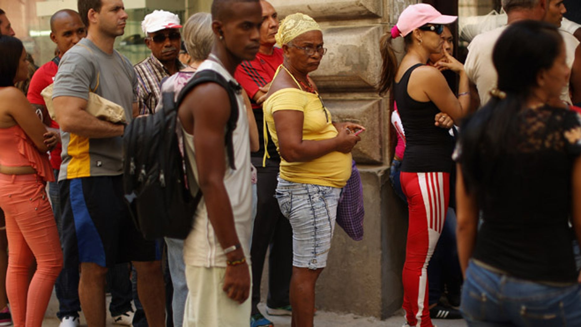 HAVANA, CUBA - AUGUST 13:  Cubans stand in line for hours outside an ETECSA state-run telecommunication store to add credit to their mobile phone accounts or activate mobile email in the old part of the city August 13, 2015 in Havana, Cuba. U.S. Secretary of State John Kerry will visit Havana Friday and raise the American flag at the reopened U.S. embassy, a symbolic act after the the two former Cold War enemies reestablished diplomatic relations in July.  (Photo by Chip Somodevilla/Getty Images)