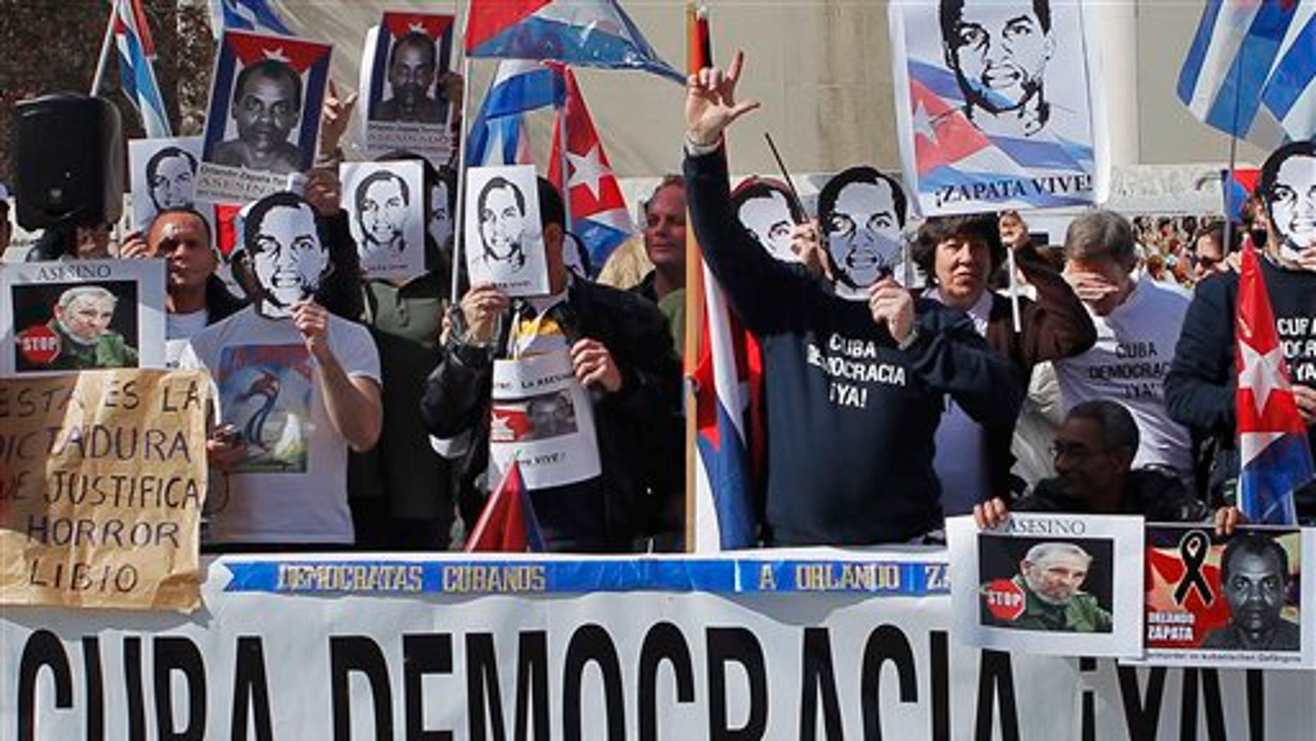 """Cuban dissidents in Spain hold a banner reading: """"Cuba democracy now!"""" during a rally outside the Cuban Embassy in Madrid Saturday Feb. 26, 2011. The protest marks the first anniversary of the death of Cuban dissident Orlando Zapata who died in Cuba after long hunger strike. (AP Photo/Andres Kudacki)"""