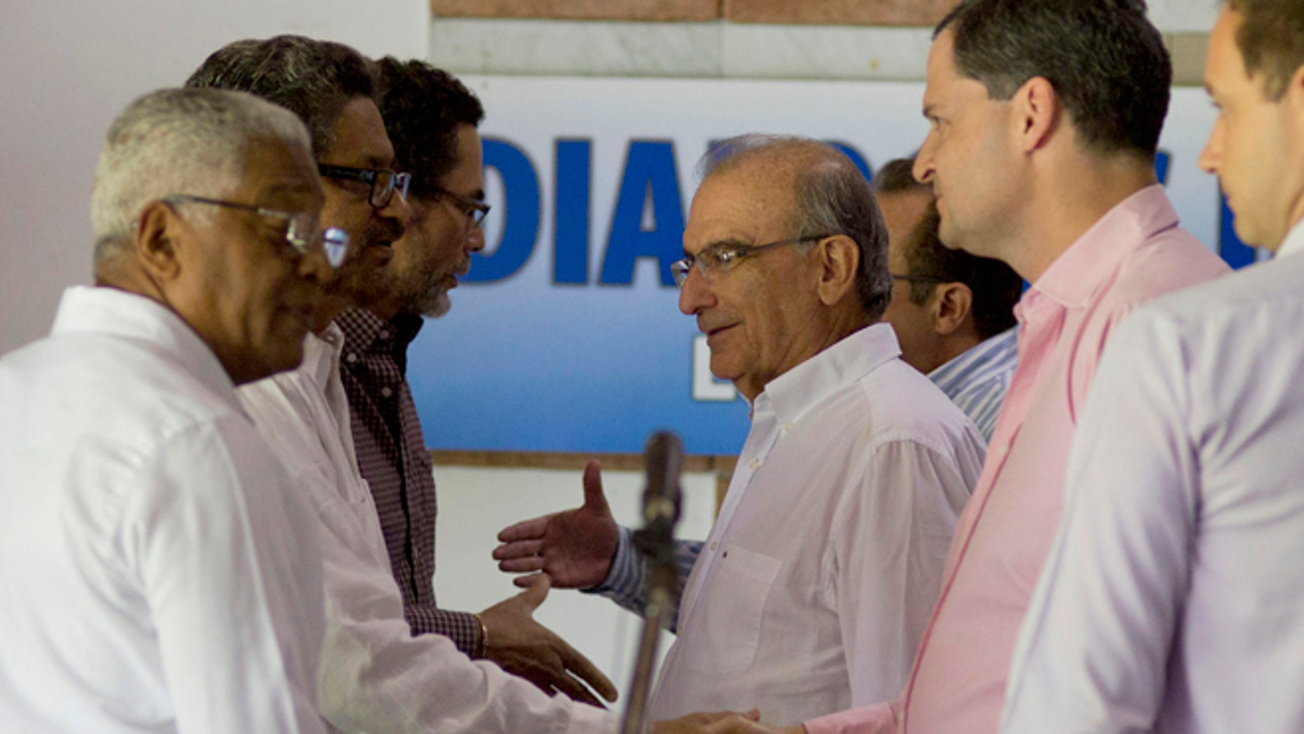 Dec. 3, 2014: Humberto de la Calle, head of Colombia's government peace negotiation team, center, talks with Ivan Marquez, chief negotiator for the Revolutionary Armed Forces of Colombia (FARC), after a joint statement in Havana, Cuba.