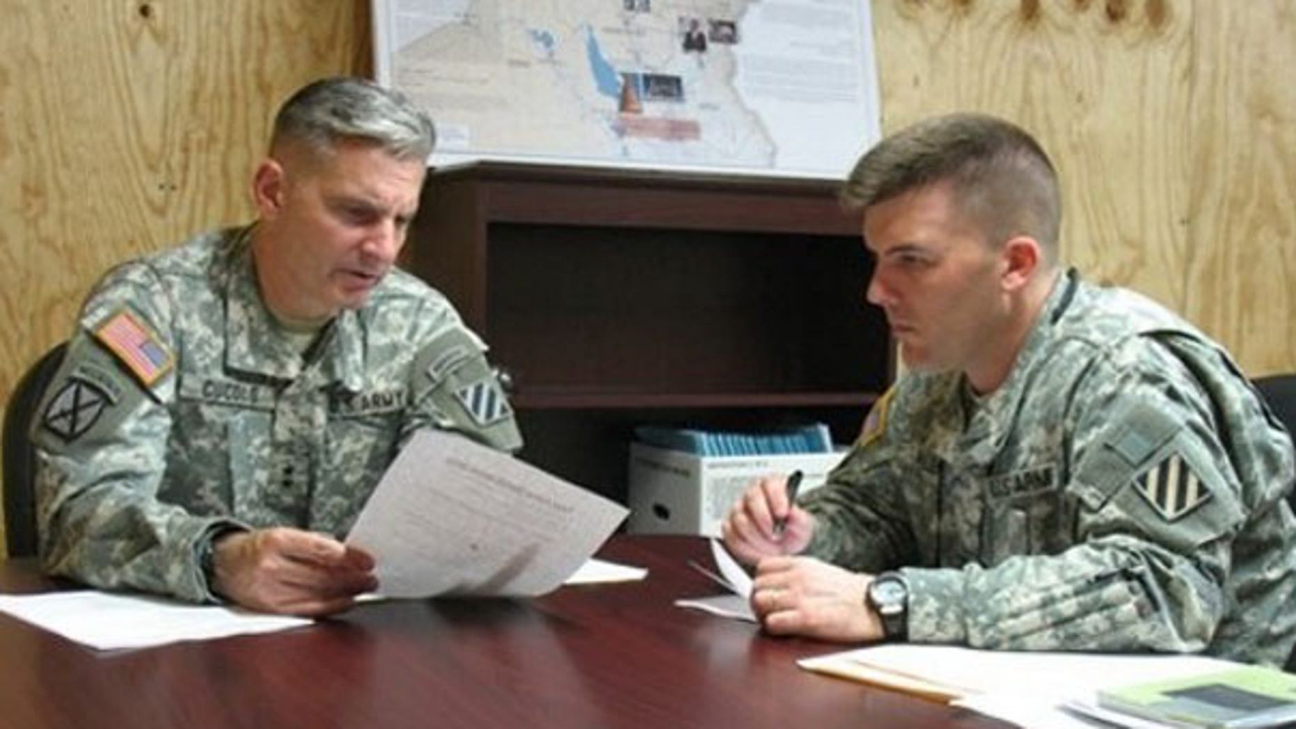 In this June 23 file photo, Maj. Gen. Anthony Cucolo, left, prepares for a mock television interview with his public affairs officer, Maj. Jeff Allen, at Fort Stewart, Ga. (AP Photo)