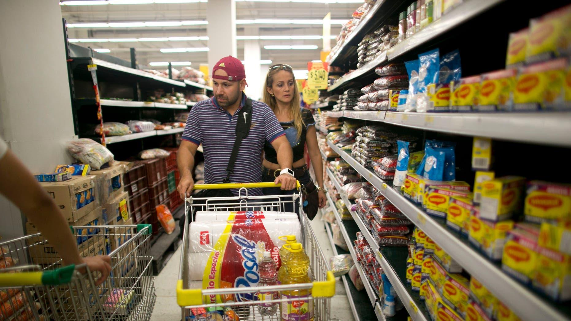 Ramiro and Tebie Gonzalez Ramirez shop for food in Cucuta, Colombia, Sunday, July 17, 2016.