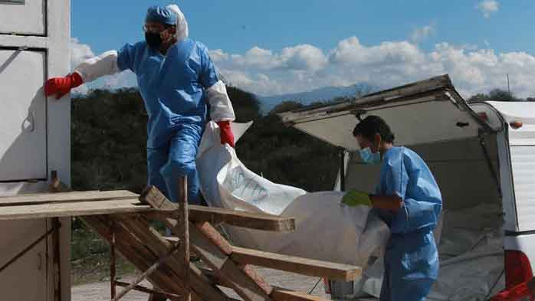 Coroner's office employees move the first of 460 bodies into the state morgue in Chilpancingo on Dec. 6, 2016.
