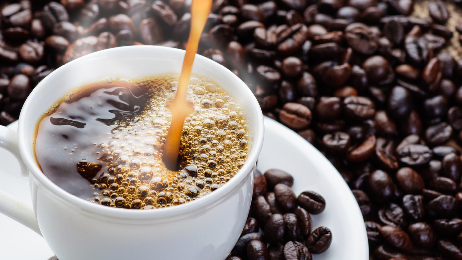 coffee pouring to cup surrounded by coffee beans