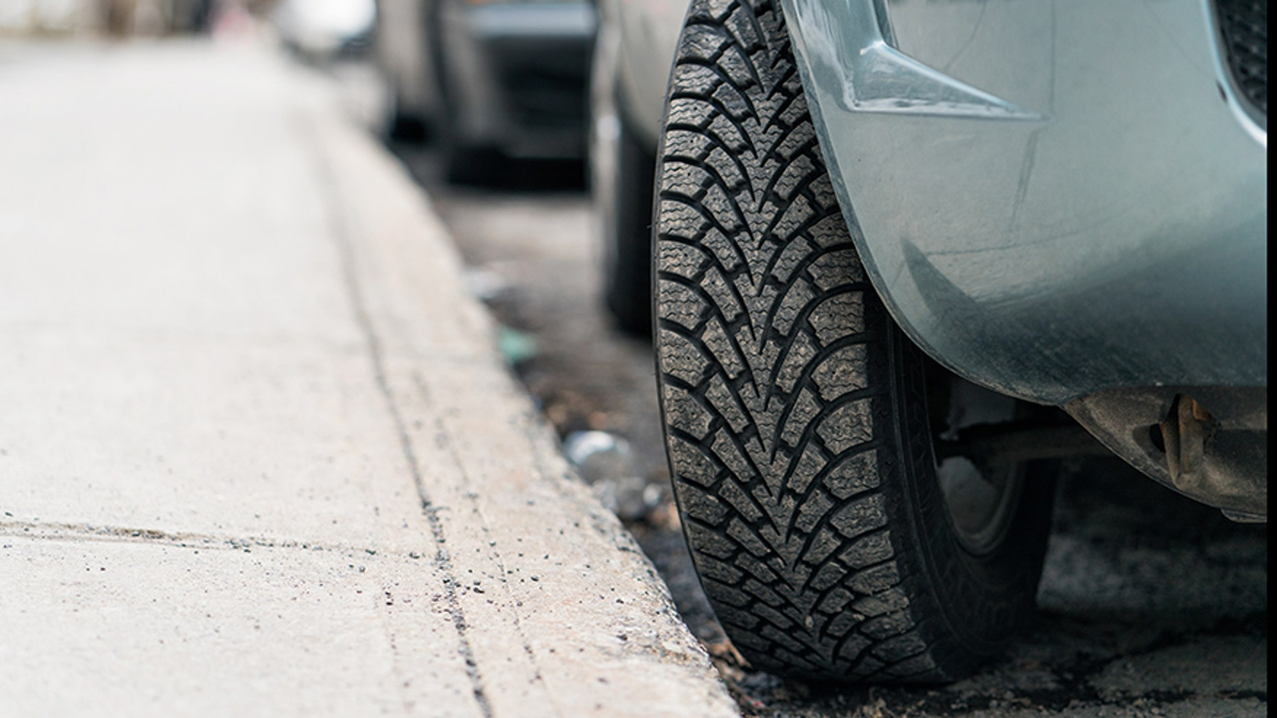 Close-up of a car parked on a hill, with the tire turned into the curb to stop  the car from rolling forward.