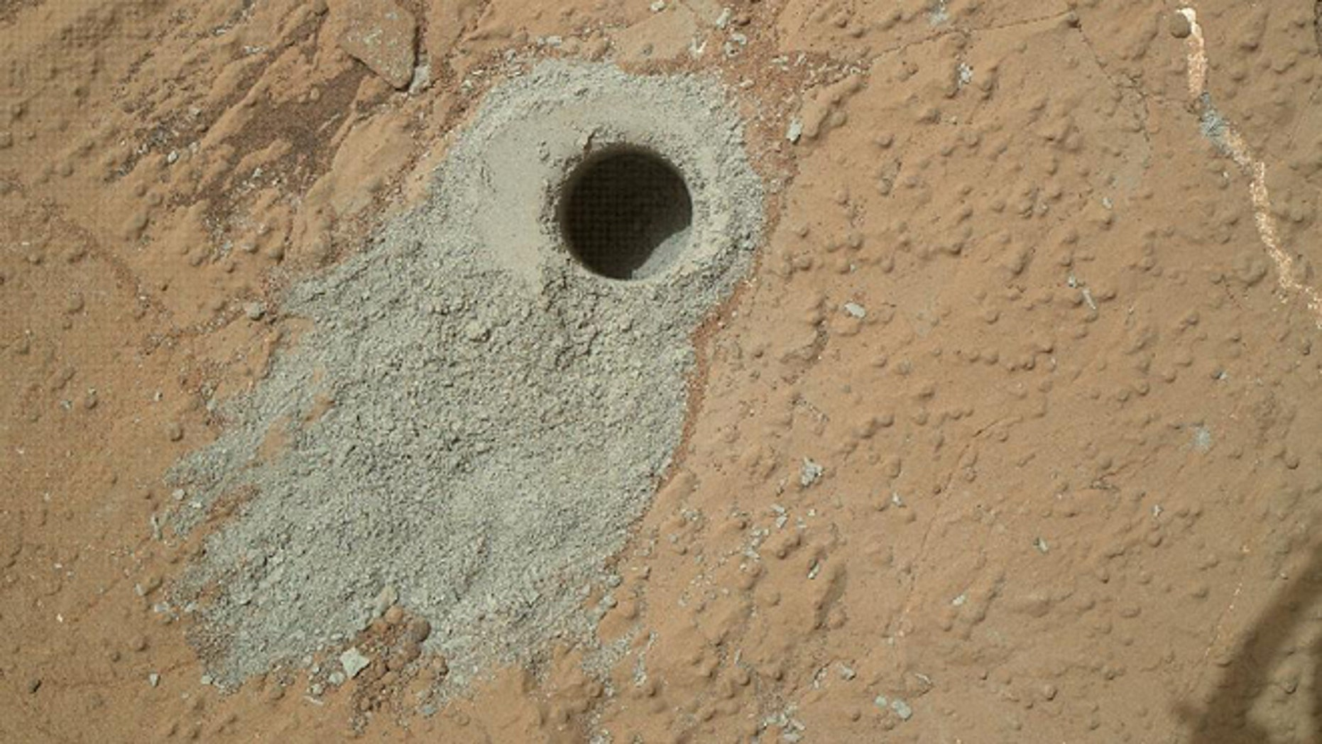 "May 19, 2013: NASA's Mars rover Curiosity drilled into this rock target, ""Cumberland,"" during the 279th Martian day, or sol, of the rover's work on Mars and collected a powdered sample of material from the rock's interior."