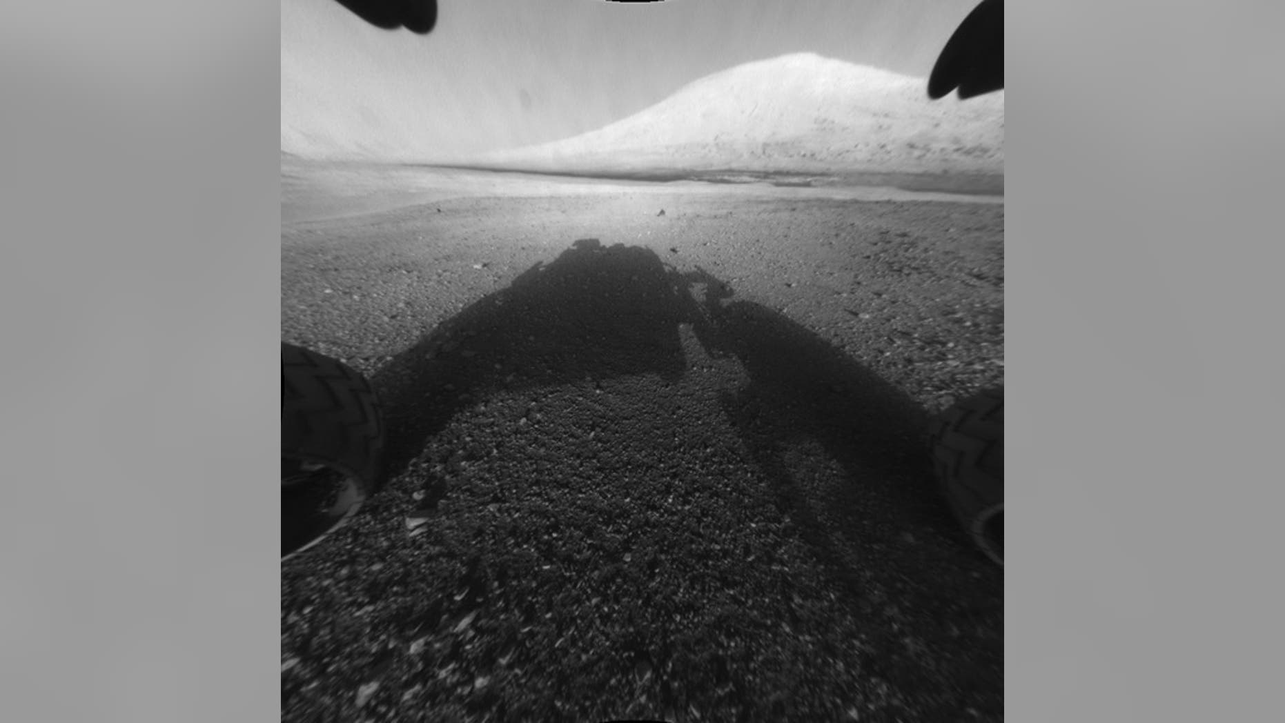 This image taken by NASA's Curiosity shows what lies ahead for the rover -- its main science target, Mount Sharp. The rover's shadow can be seen in the foreground, and the dark bands beyond are dunes.