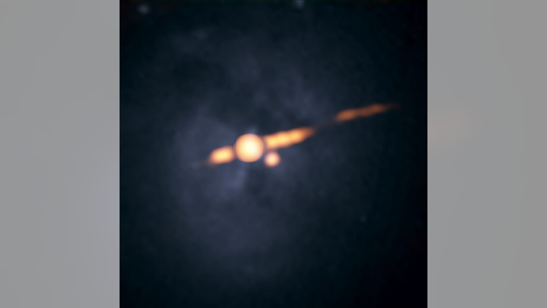 A radio image of the galaxy Cygnus A captured by the Very Large Array (VLA) in 2015 (orange), overlaid on a photo by NASA's Hubble Space Telescope. The orange dot below and to the right of the larger orange circle at the galaxy's center is the suspected second supermassive black hole.