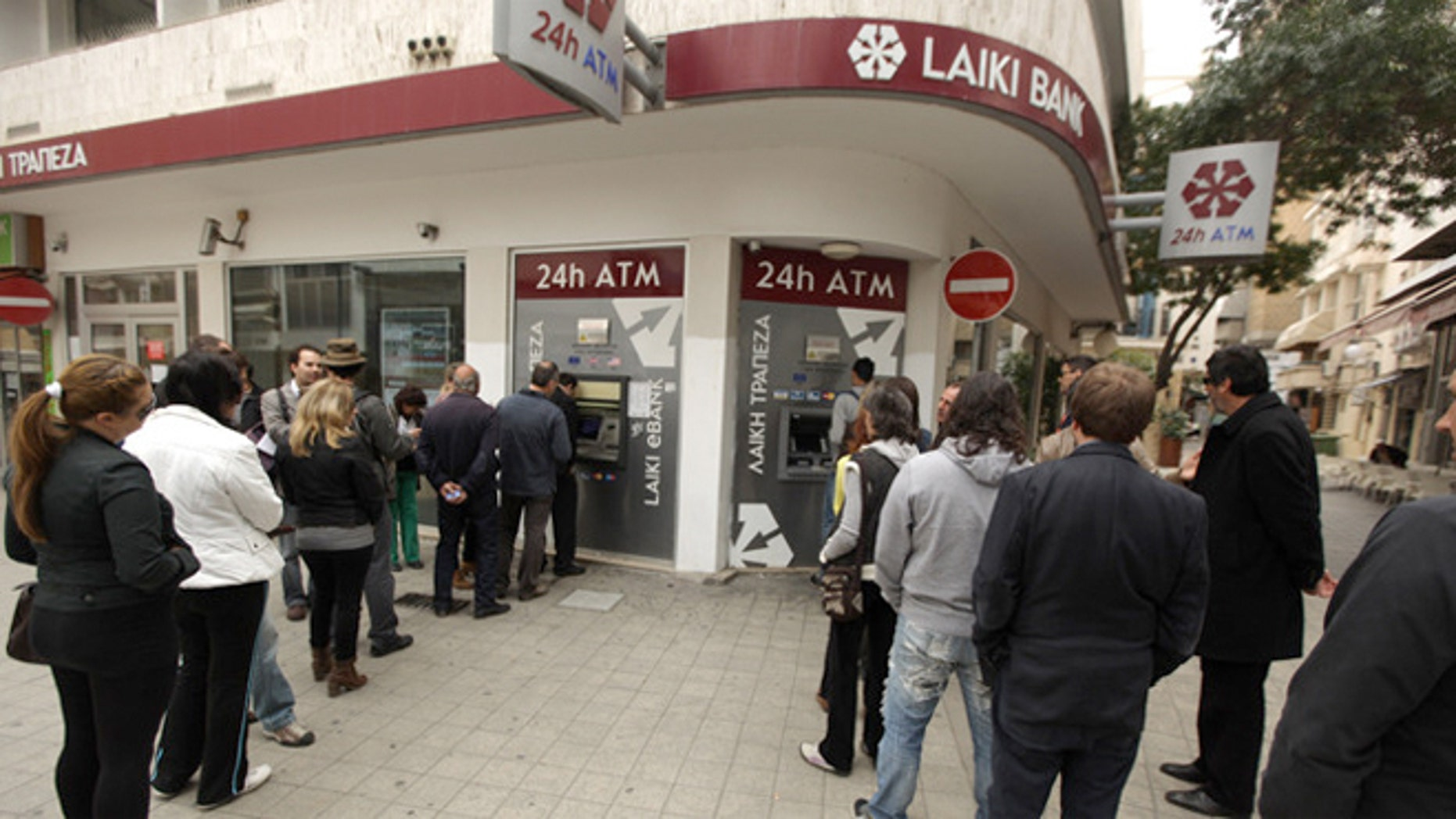 People in Cyrpus wait in line to withdraw money from an ATM of a Laiki Bank in the old city of the capital, Nicosia.