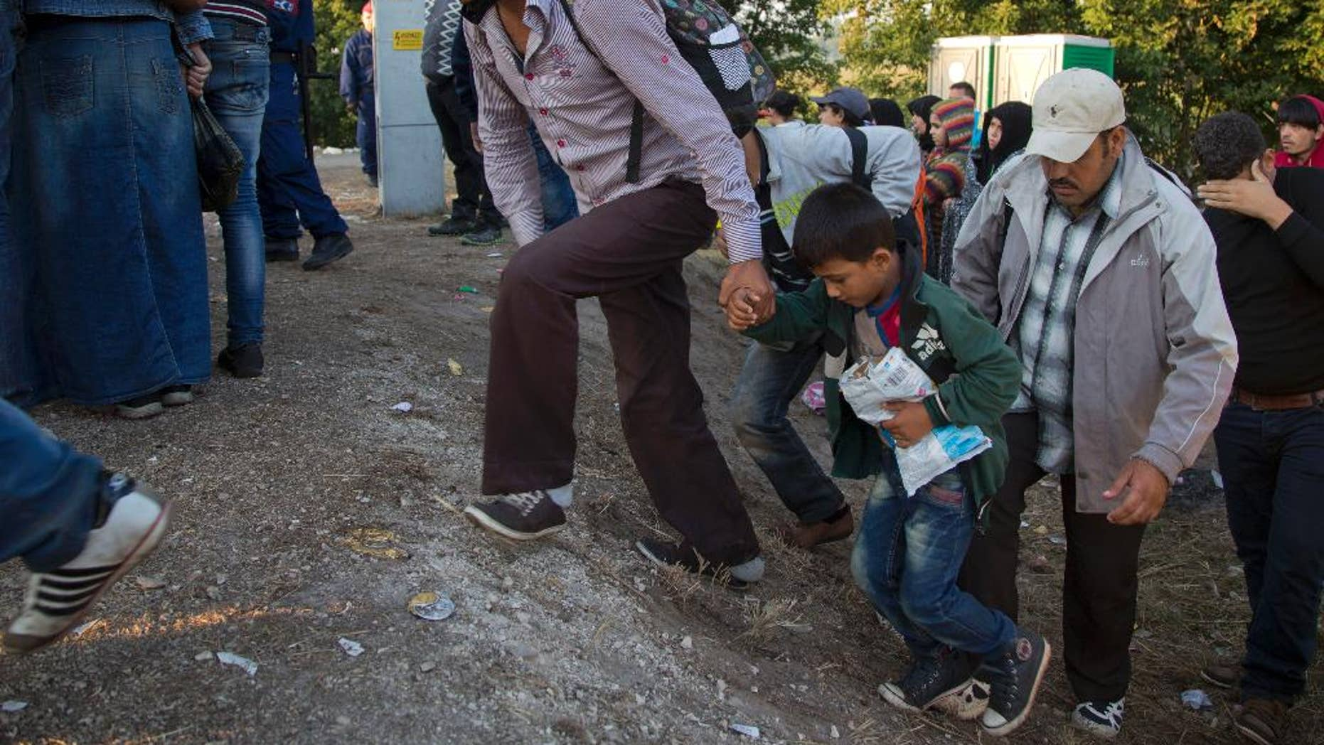 Aug. 31, 2015: Refugees who crossed the border from Serbia climb on a road to board a bus to transfer them to a refugee camp, in Asotthalom, Hungary. Migrants fearful of death at sea in overcrowded and flimsy boats have increasingly turned to using a land route to Europe through the Western Balkans.