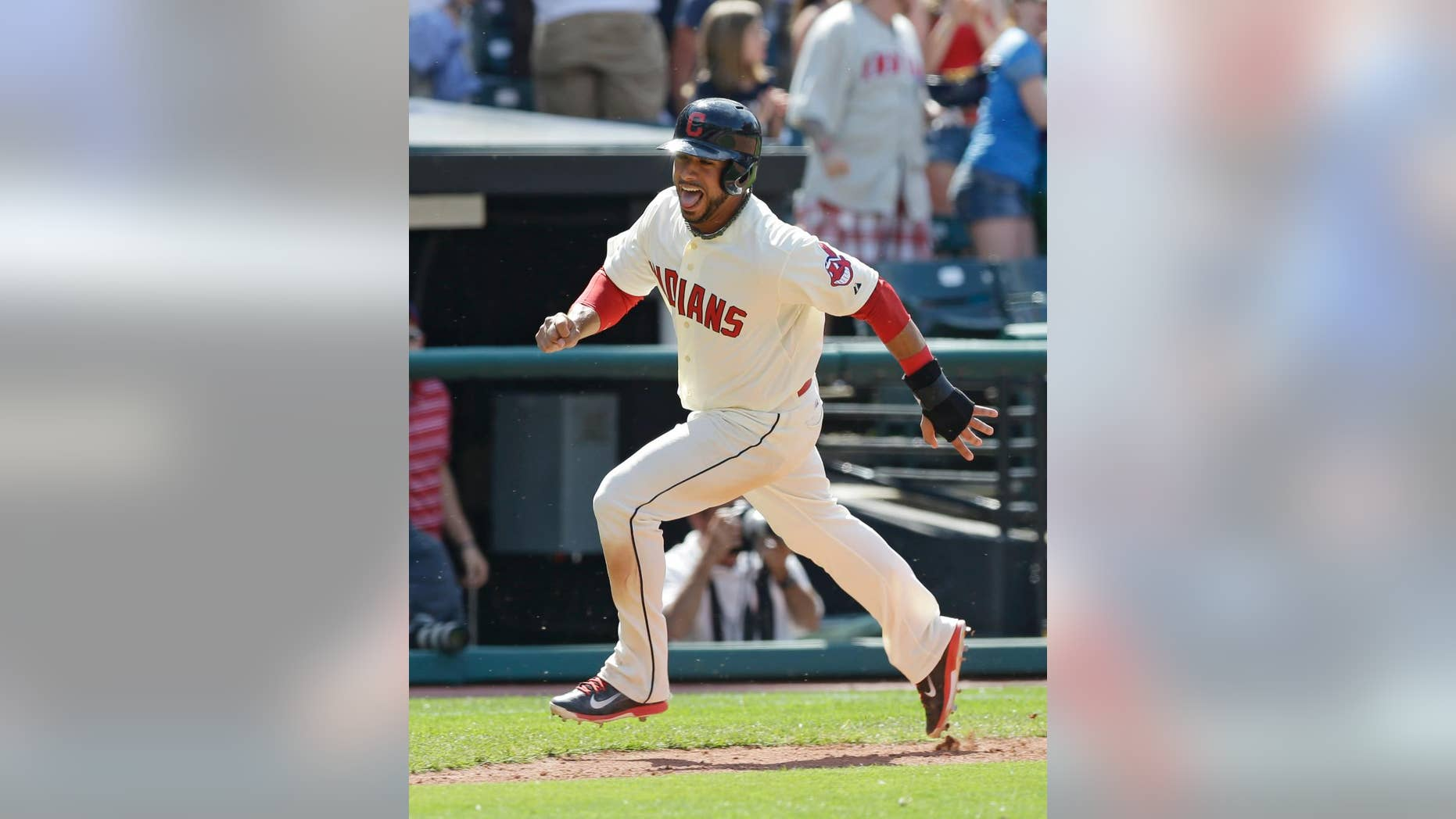 Cleveland Indians' Mike Aviles scores on a game-winning two-run home run hit by Michael Bourn in the ninth inning of a baseball game against the Colorado Rockies, Sunday, June 1, 2014, in Cleveland. The Indians defeated the Rockies 6-4. (AP Photo/Tony Dejak)