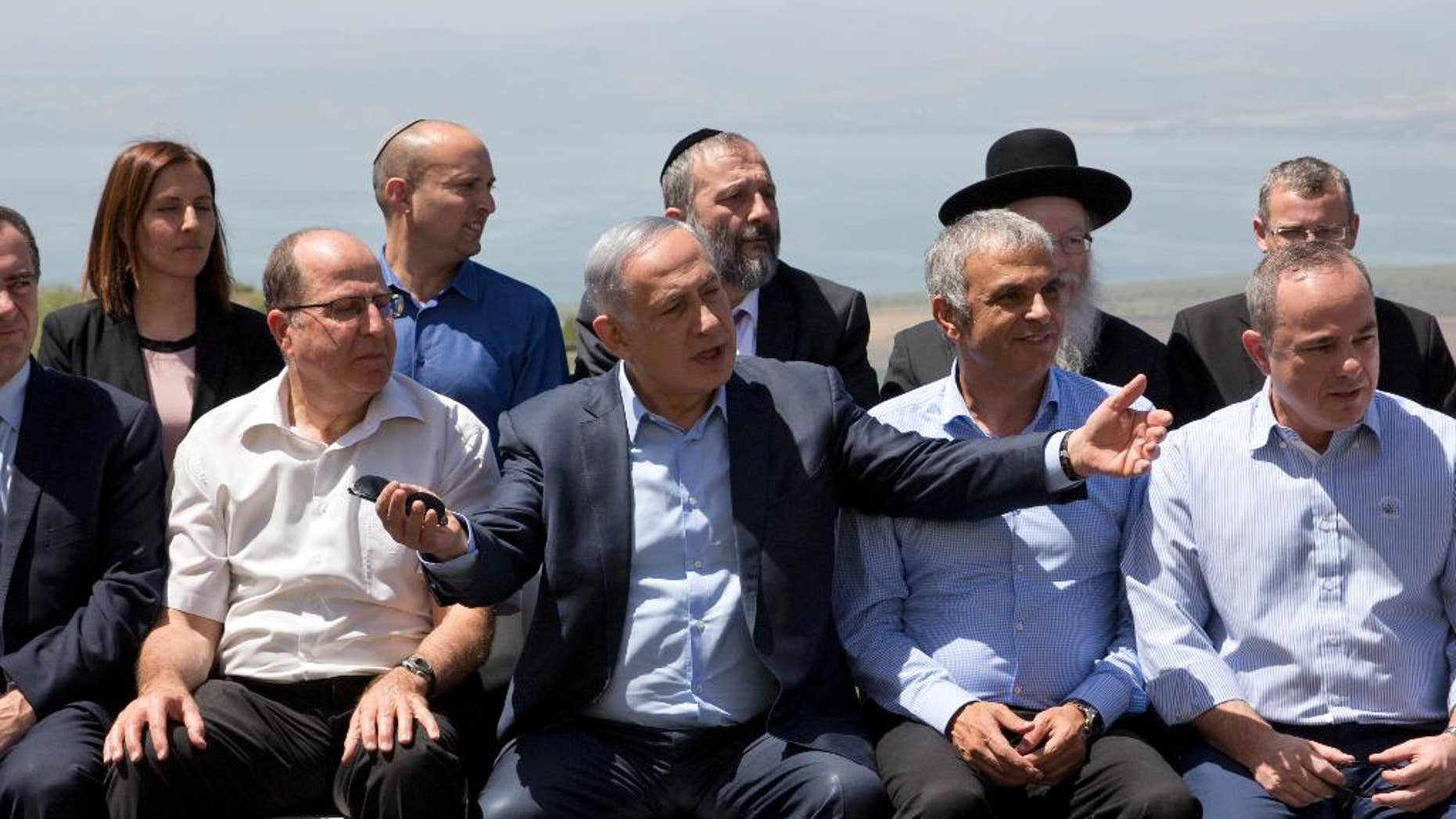 File - In this Sunday, April 17, 2016 file photo, Israeli Prime Minister Benjamin Netanyahu, center, poses with ministers prior to the weekly cabinet meeting in the Israeli controlled Golan Heights. Netanyahu has sparked a new diplomatic brushfire by declaring that the Golan Heights, seized from Syria in the 1967 war, is and should remain sovereign Israeli territory. But following some tough international criticism, Israeli officials have begun to backtrack, saying that a 1981 decision to apply Israeli law to the strategic plateau fell short of annexation and implying that Netanyahu misspoke. (AP Photo/Sebastian Scheiner, File)