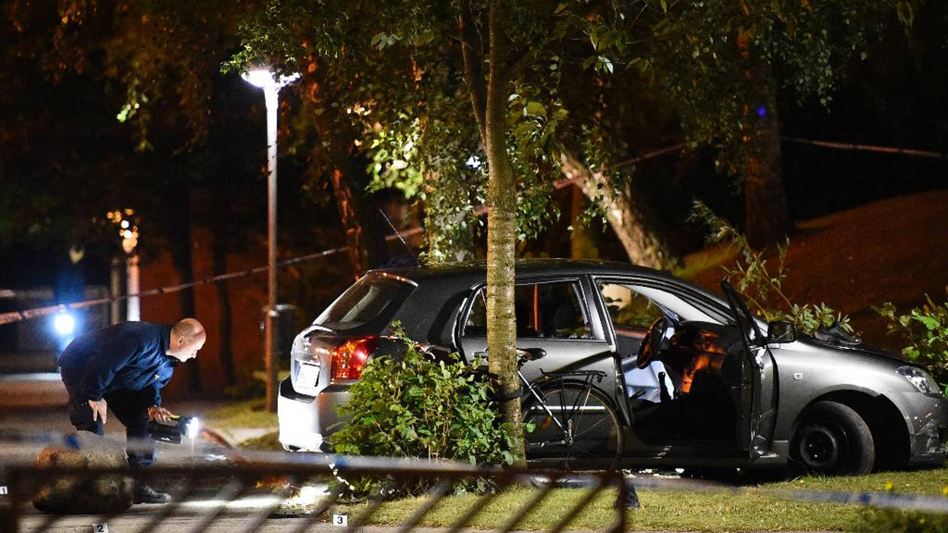 Police examine the scene of a shooting in southern Malmo, Sweden, Sunday Sept. 25, 2016. Swedish police say four people have been wounded in a shooting in Malmo, after gunmen on motor scooters opened fire Sunday evening on a car they had been chasing through a neighborhood. (Emil Langvad/TT via AP)