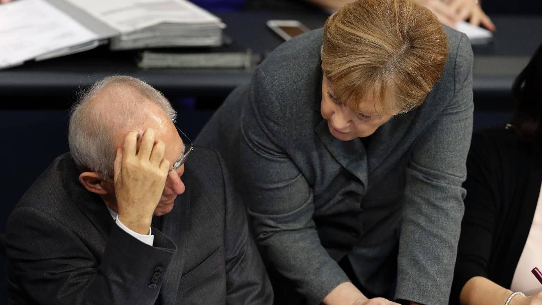 German Chancellor Angela Merkel, right, and German Finance Minister Wolfgang Schaeuble, left, talk during a budget debate as part of a meeting of the German Federal Parliament, Bundestag, at the Reichstag building in Berlin, Germany, Tuesday, Nov. 22, 2016. (AP Photo/Michael Sohn)