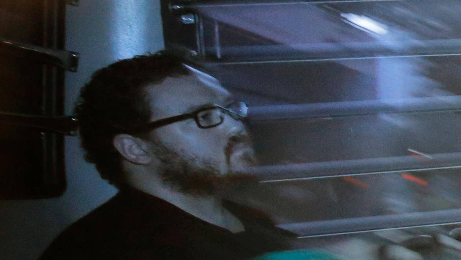 Rurik Jutting sitting in a prison bus in 2014.