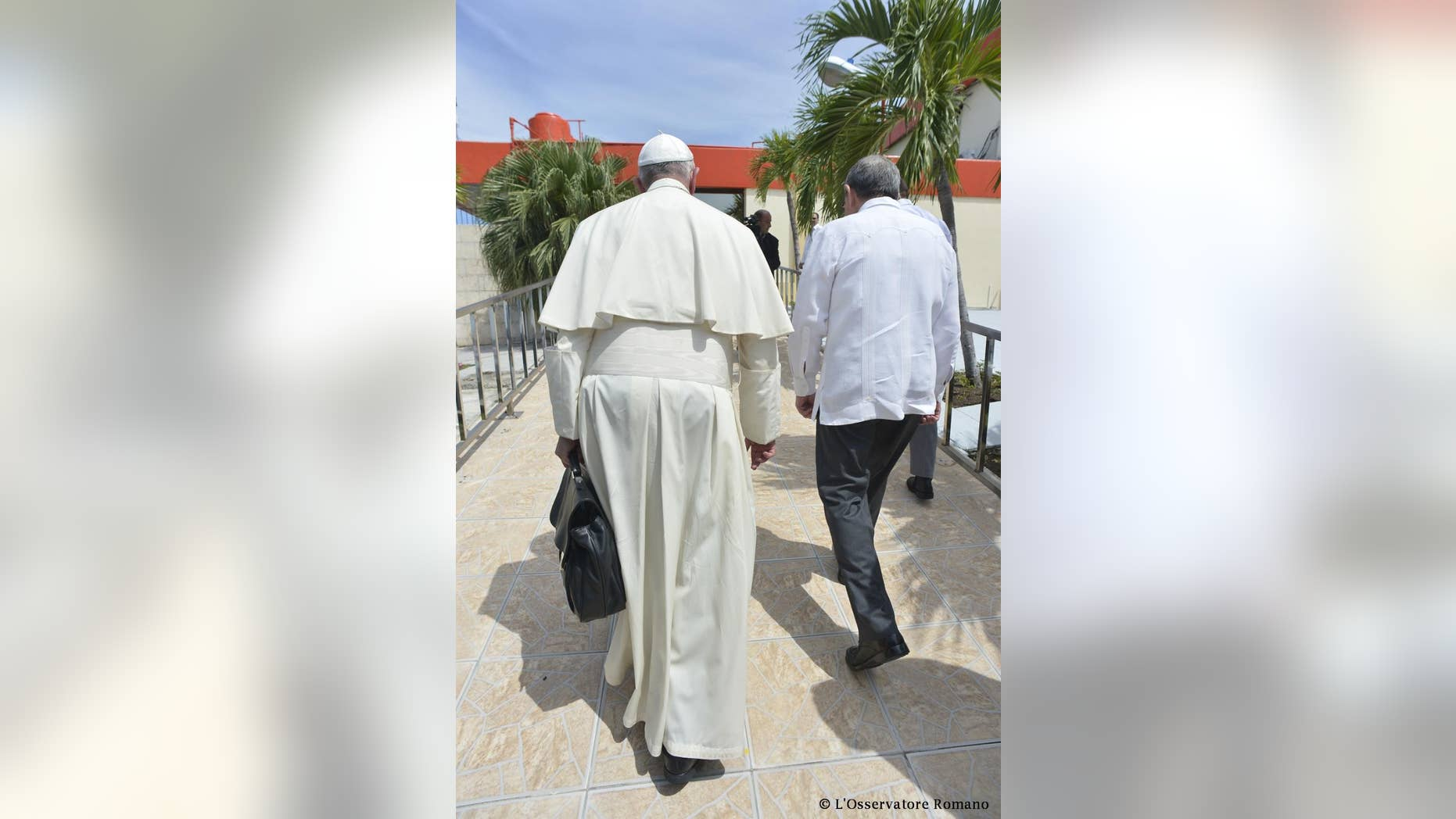In this photo taken Tuesday, Sept. 22, 2015, Pope Francis talks with Cuba's President Raul Castro during his farewell ceremony at the airport in Santiago, Cuba. Pope Francis wrapped up his visit to Cuba Tuesday by celebrating Mass at the country's most revered shrine and giving a pep talk with families before flying north to Washington for the start of his U.S. tour. (L'Osservatore Romano/Pool Photo via AP)