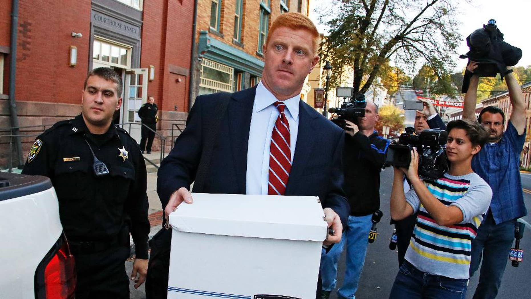 Former Penn State University assistant football coach Mike McQueary, center, leaves the Centre County Courthouse Annex in Bellefonte, Pa., Monday, Oct. 17, 2016. The trial for McQueary's defamation and whistleblower lawsuit against Penn State over how it treated him for complaining about assistant football coach Jerry Sandusky sexually abusing a boy got underway with opening arguments on Monday. (AP Photo/Gene J. Puskar)