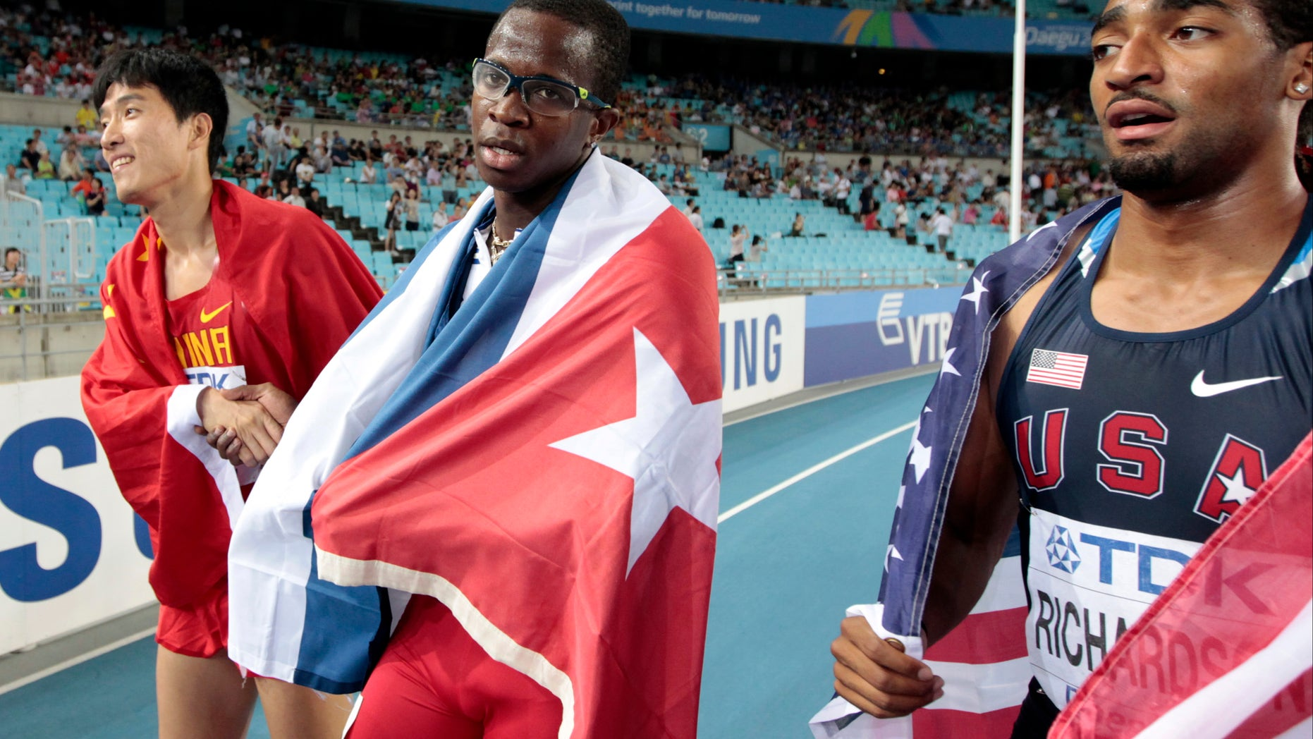 Aug. 29: Cuba's Dayron Robles, center,  walks with Cuban flag, after crossing the finish line first in the Me'n's 110m Hurdles final at the World Athletics Championships in Daegu, South Korea. Robles finished first but was later disqualified for making contact with China's Liu Xiang, left.