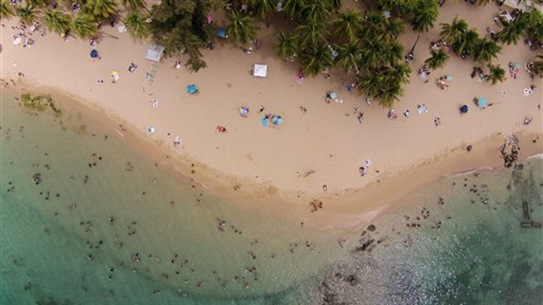 This July 16, 2014, photo, shows an aerial view of people enjoying the beach in San Juan, Puerto Rico. The territory's government has managed its first balanced budget in more than a decade. Sales tax revenues are up and its publicly owned power company has won breathing room to pay its debts. (AP Photo/Ricardo Arduengo)