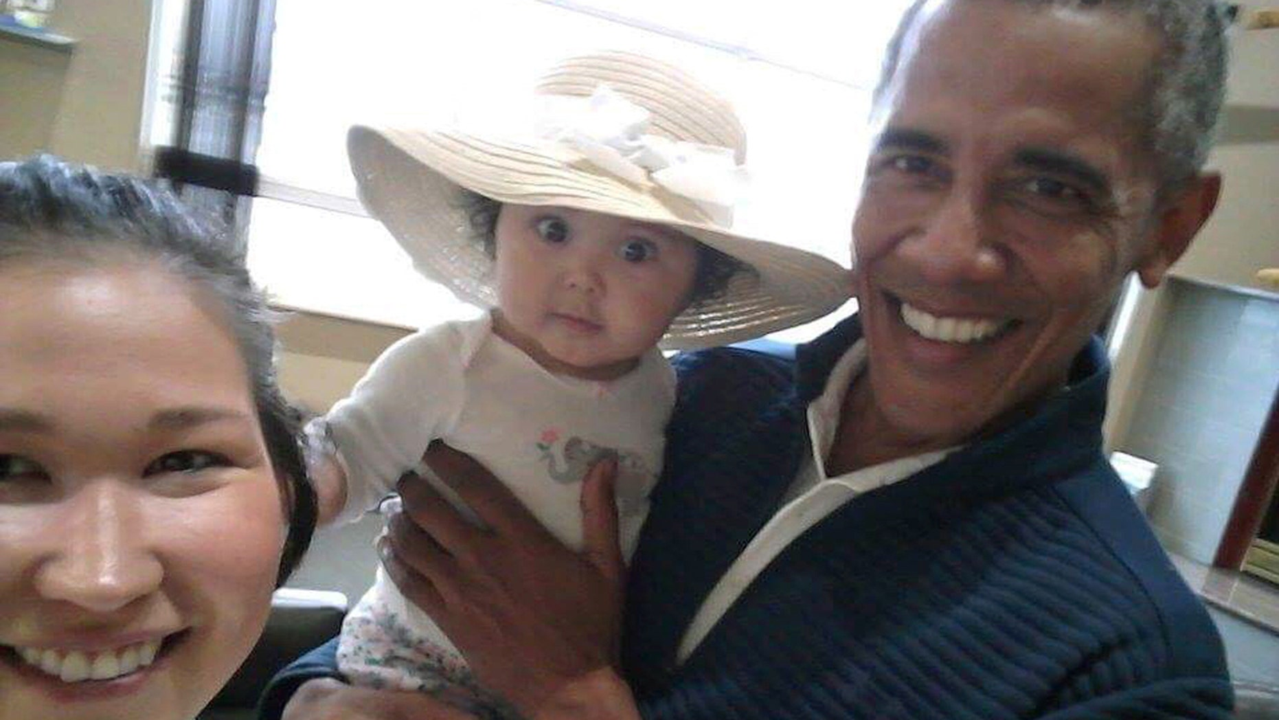 """July 3: .S. President Barack Obama holds Jackinsky's 6-month-old baby girl while posing for a selfie with the pair at a waiting area at Anchorage International Airport, in Anchorage, Alaska. Jackinsky said Obama walked up to her and asked, """"Who is this pretty girl?"""""""