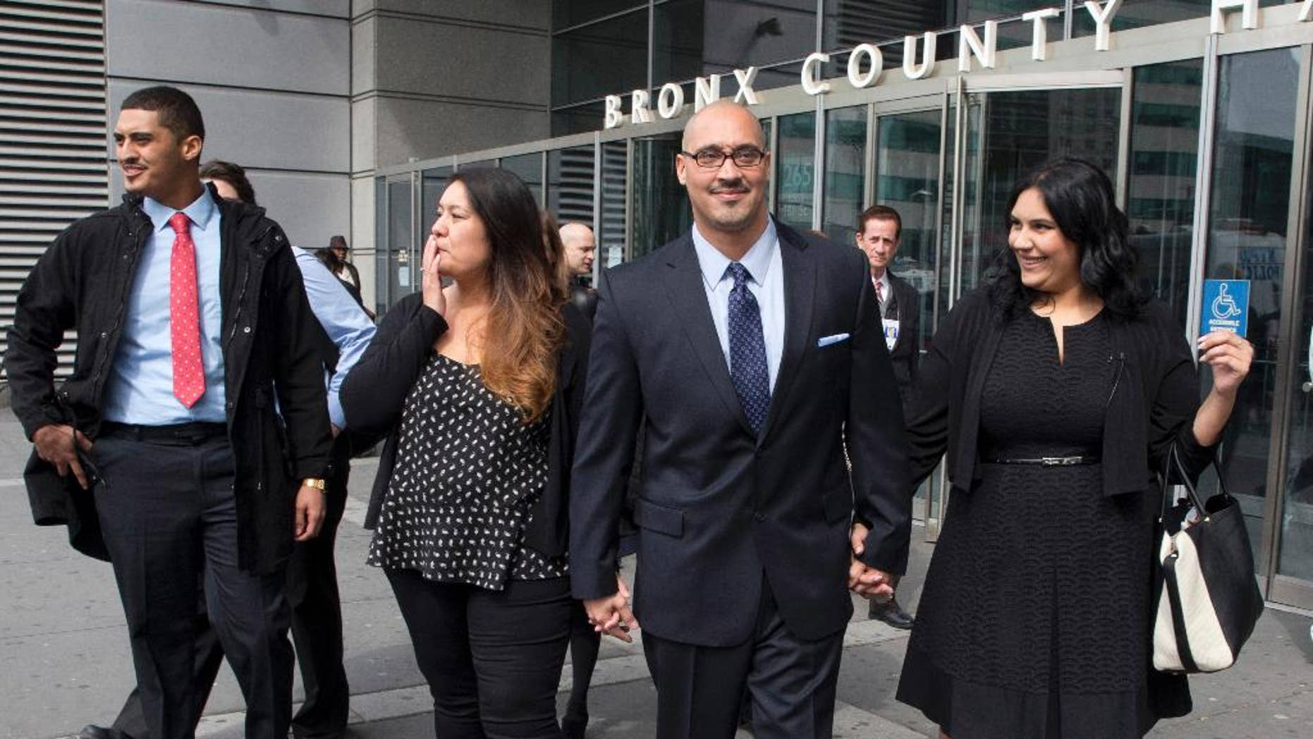 FILE- In this March 23, 2016 file photo, Richard Rosario, center, is joined by his daughter Amanda, right, son Richard Jr., left, and wife Minerva as he leaves Bronx state Supreme Court in New York after his conviction was overturned. Rosario, who spent 20 years in prison for a killing he says happened while he was in Florida, made an unusual request to keep his case open for more investigation, with hopes that newfound evidence would support is claim of innocence, not just that his ex-lawyers erred, but a judge said no. (AP Photo/Mary Altaffer, File)