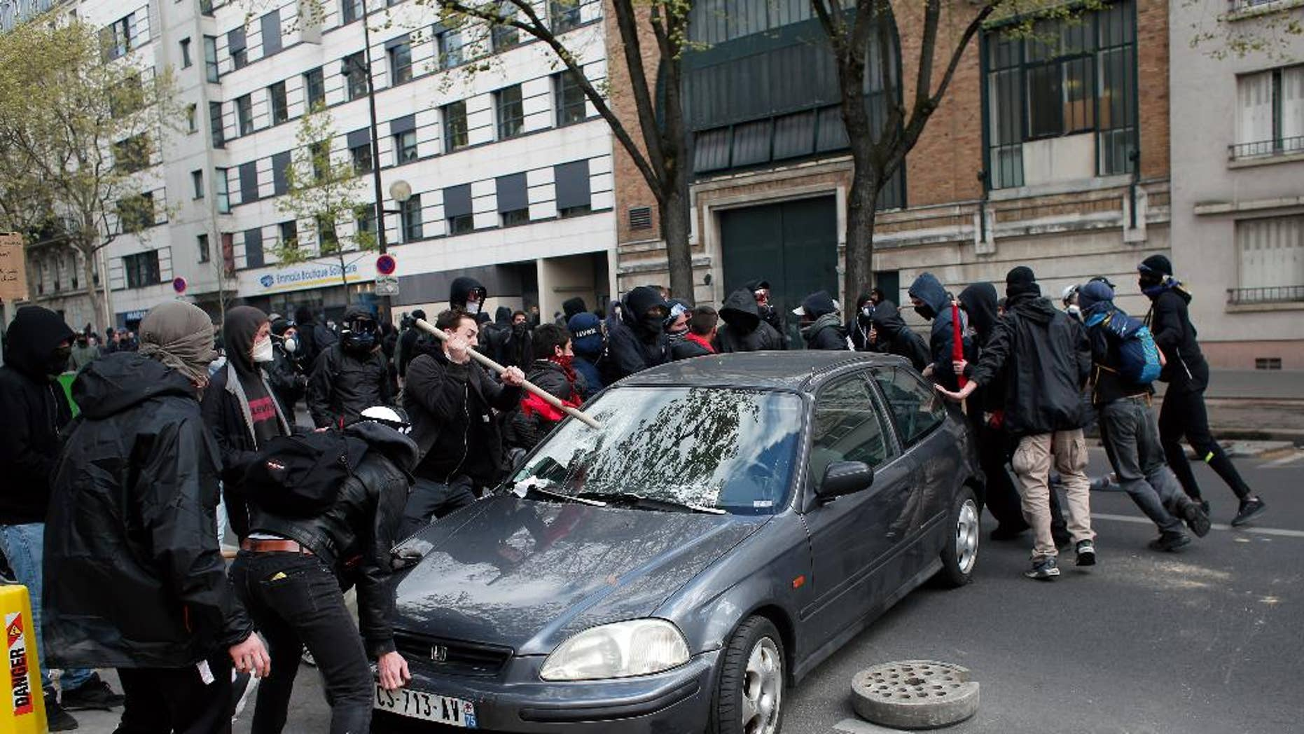 Protestors damage a car during clashes with riot police officers as part of a demonstration against the proposed changes to France's working week and layoff practices, in Paris, Thursday, April 28, 2016. Protesters across France are again marching to voice their anger at labor reforms being championed by the country's Socialist government. (AP Photo/Thibault Camus)