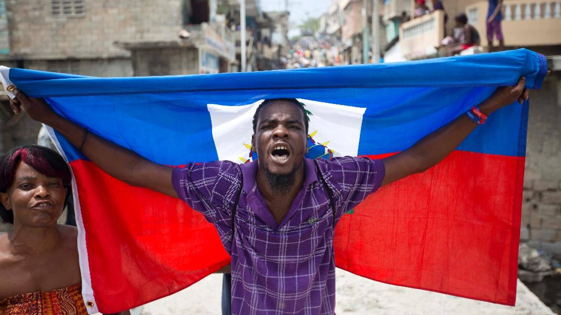 A supporter of presidential candidate Maryse Narcisse marches with a Haitian national flag during a demonstration in support of interim President Jocelerme Privert in Port-au-Prince, Haiti, Tuesday, June 14, 2016. Haiti's legislators will decide whether to pave way for a new interim leader until elections can be resolved or extend the term for Privert, whose 120-day mandate is due to expire today. ( AP Photo/Dieu Nalio Chery)