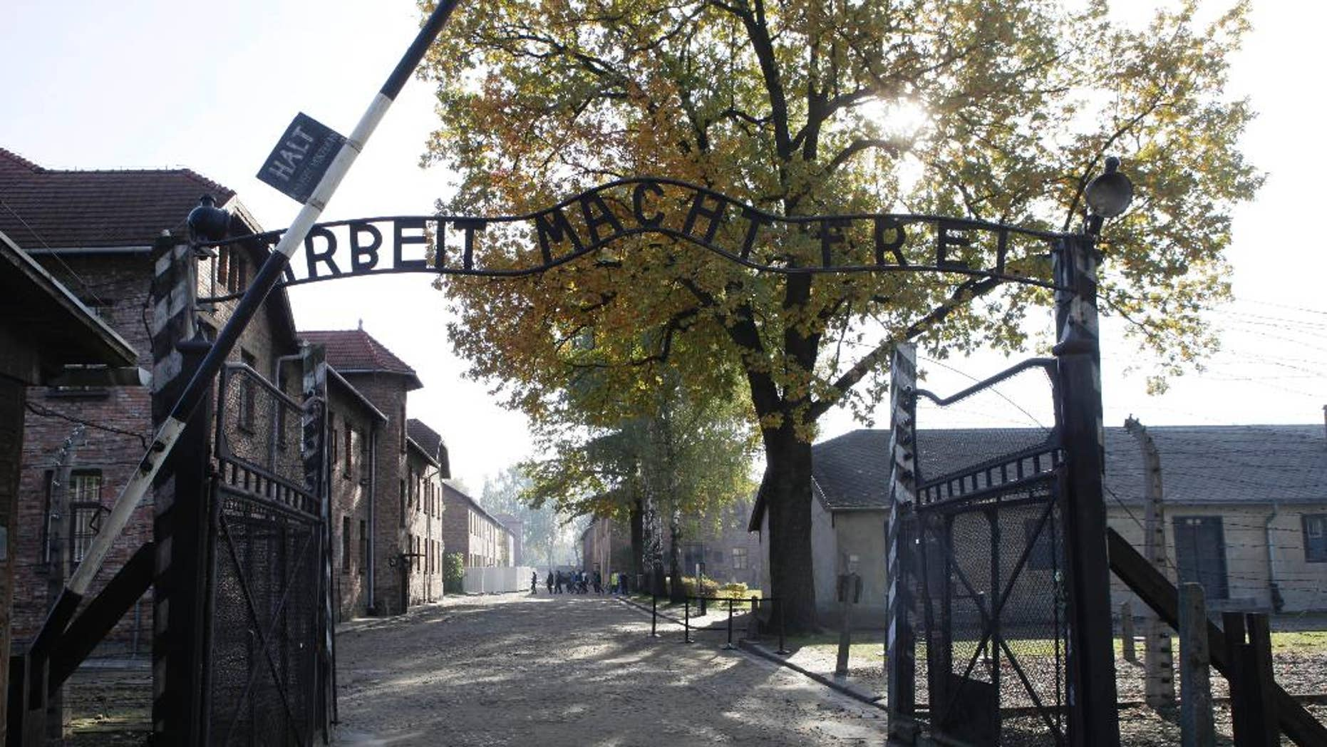 """File - In this Oct. 19, 2012 file photo the entrance with the inscription """"Arbeit Macht Frei"""" (Work Sets You Free) gate of the former German Nazi death camp of Auschwitz is seen at the Auschwitz-Birkenau memorial in Oswiecim, Poland. A group of nearly a dozen people took off their clothes, killed a sheep and chained themselves together by the gate before being detained by police, Friday, March 24, 2017.  (AP Photo/Czarek Sokolowski,file)"""