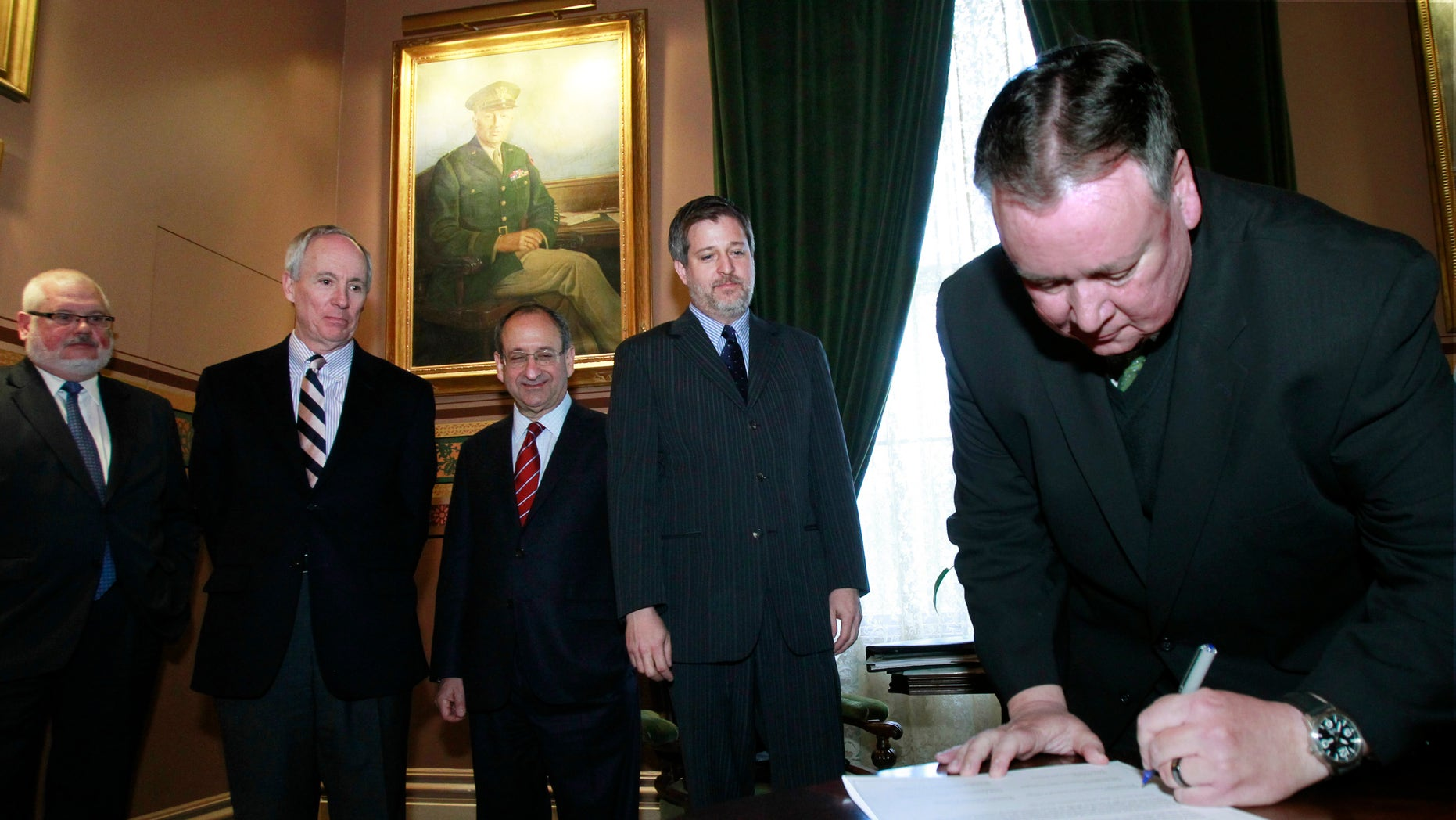 Vermont Technical College President Phil Conroy, right, signs a memorandum of understanding to create the Vermont Higher Education Food Systems Consortium on Thursday, Nov. 7, 2013, in Montpelier, Vt. The institutions plan to share courses in agriculture and food so that students enrolled at one school can take a course, do research or get an internship at another college. Looking on are, from left, Vermont State Colleges Chancellor Tim Donovan, University of Vermont President Thomas Sullivan, Vermont Law School Dean Marc Mihaly and Sterling College President Matthew Allen Derr. (AP Photo/Toby Talbot)