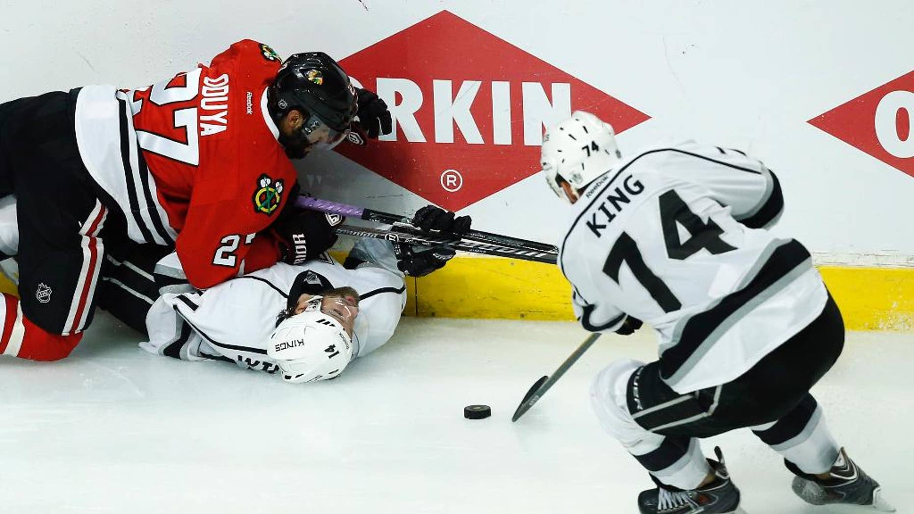 Los Angeles Kings left wing Dwight King (74) takes the puck as Chicago Blackhawks defenseman Johnny Oduya (27) and the Kings right wing Justin Williams (14) battle during the overtime period in Game 5 of the Western Conference finals in the NHL hockey Stanley Cup playoffs Wednesday, May 28, 2014, in Chicago. (AP Photo/Andrew A. Nelles)
