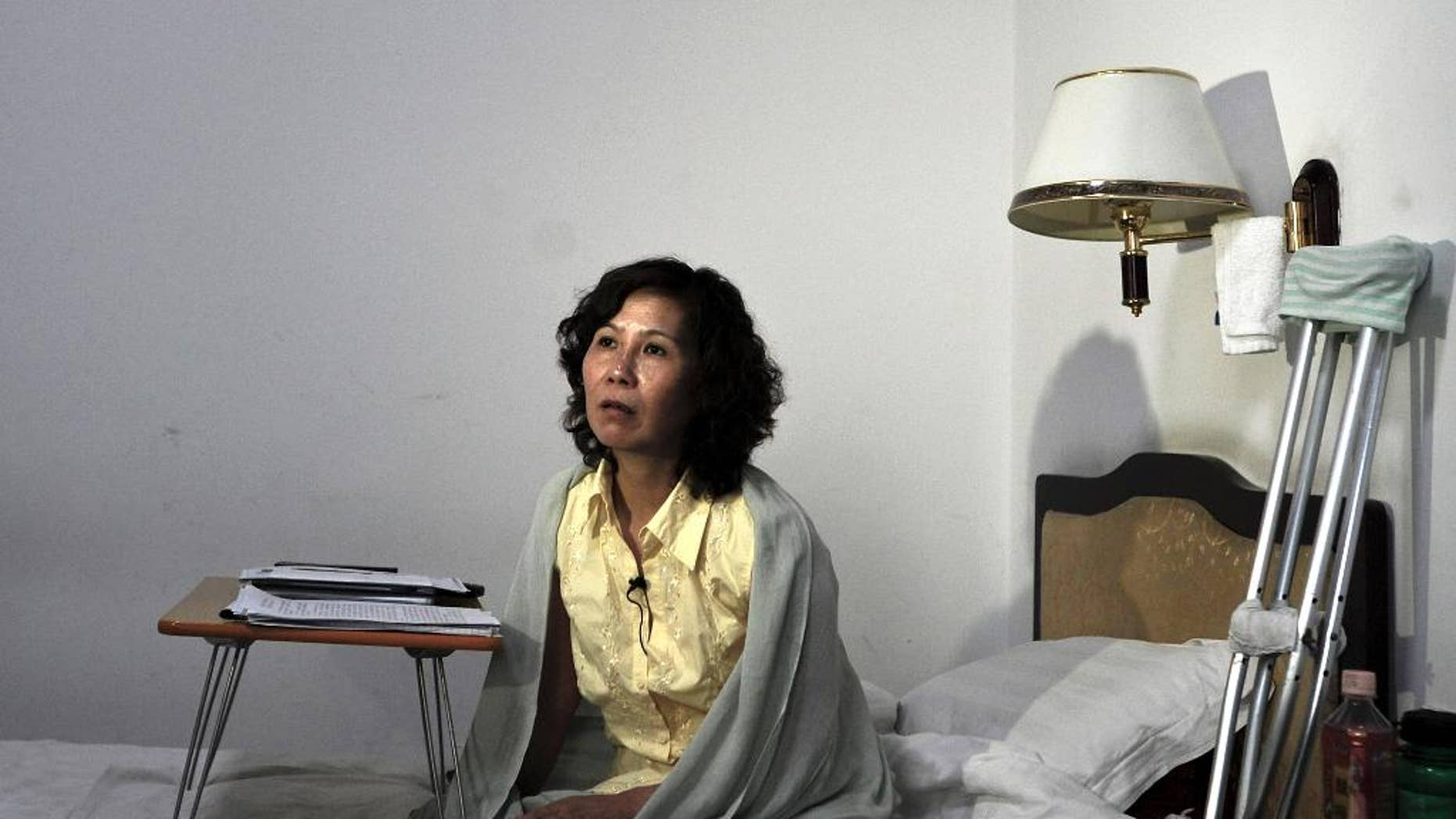 FILE - In this June 30, 2010, file photo, Chinese lawyer Ni Yulan sits on a bed in a hotel in Beijing. Ni was awarded the State Department's International Women of Courage Award for her work defending people forcibly evicted from their homes. Ni said that police stopped five Western diplomats who were trying to visit her in Beijing on Saturday, April 23, 2016, after she had been prevented from travelling to the United States to accept the award for her rights work. (AP Photo/Andy Wong, File)