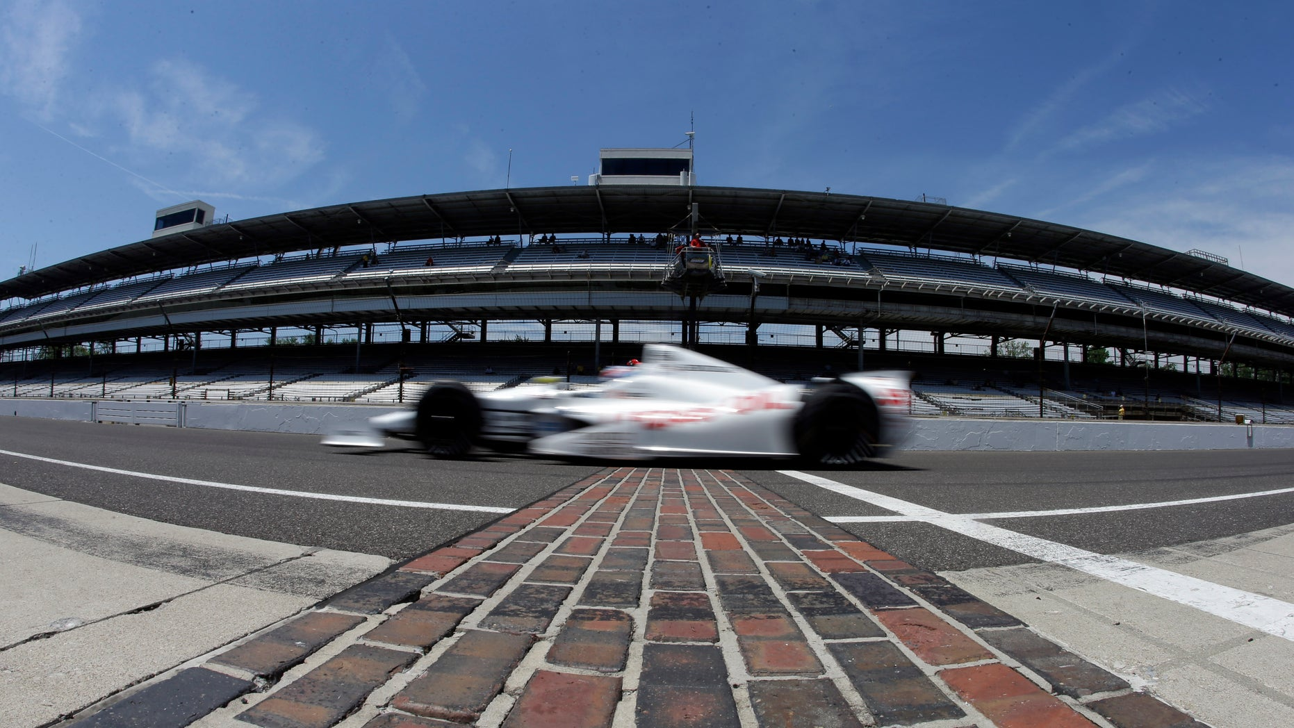 In this photo taken with a fisheye lens, Tristan Vautier, of France, drives across the start/finish line as he leaves the pit area during practice for the Indianapolis 500 auto race at the Indianapolis Motor Speedway in Indianapolis, Wednesday, May 15, 2013. (AP Photo/Darron Cummings)