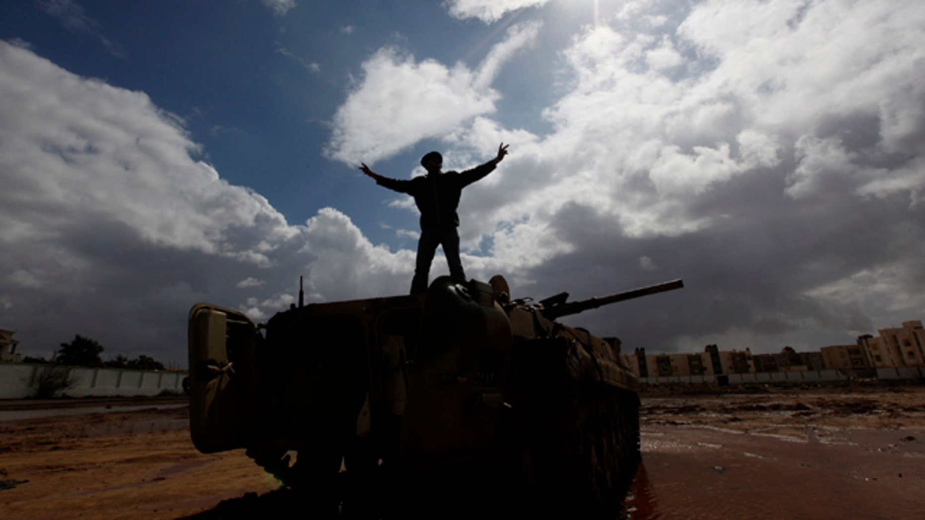 Feb. 24, 2011: A Libyan man stands over a destroyed tank as he flashes V signat Al-Katiba military base after it fell to anti-Libyan Leader Moammar Gadhafi protesters few days ago