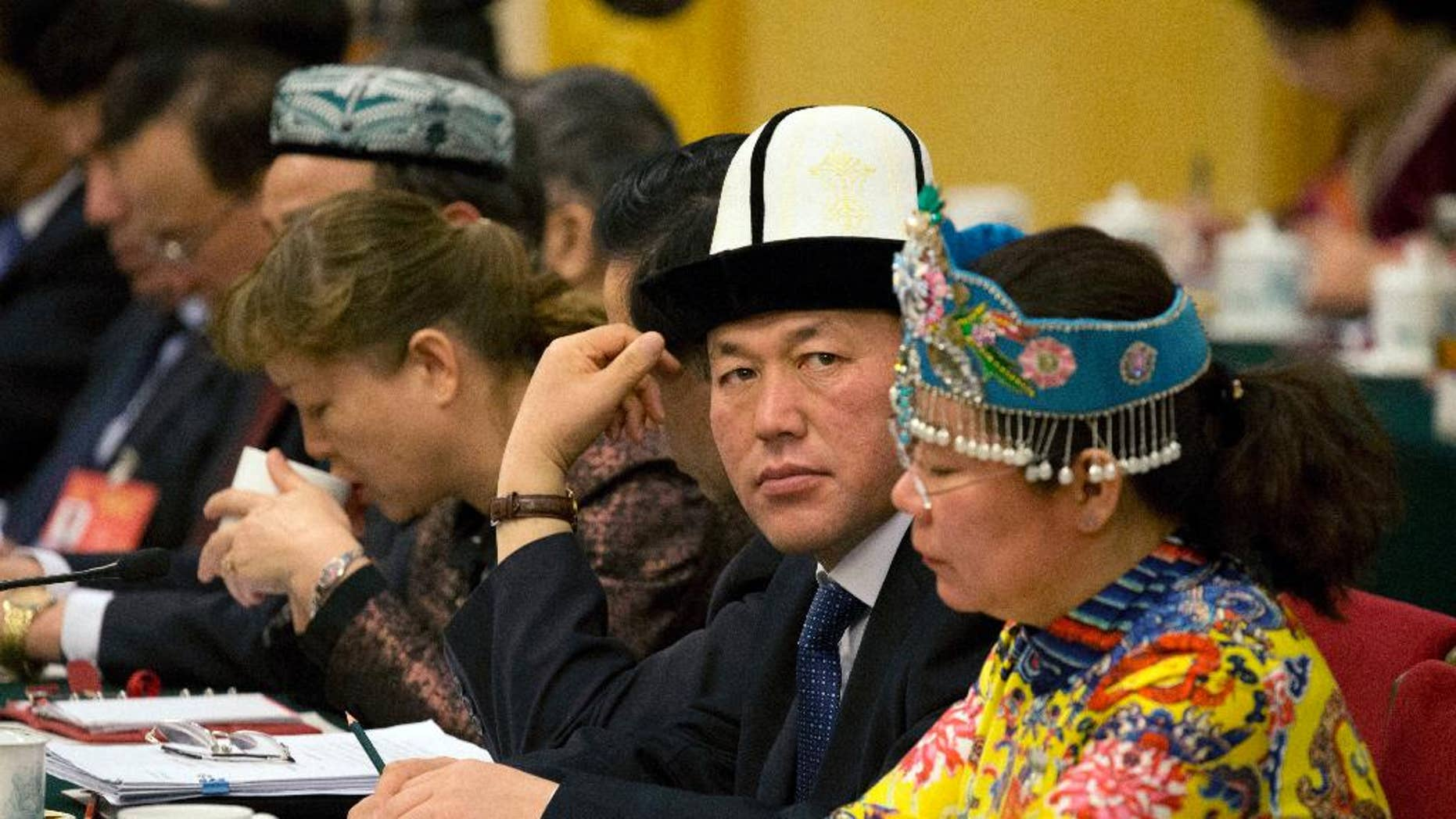 Delegates from Xinjiang meet in the Xinjiang Hall of the Great Hall of the People on the sideline of the National People's Congress in Beijing, China, Sunday, March 12, 2017. China's ruling Communist Party is hardening its rhetoric about Islam, with top officials making repeated warnings this past week about the specter of global religious extremism seeping into the country. (AP Photo/Ng Han Guan)