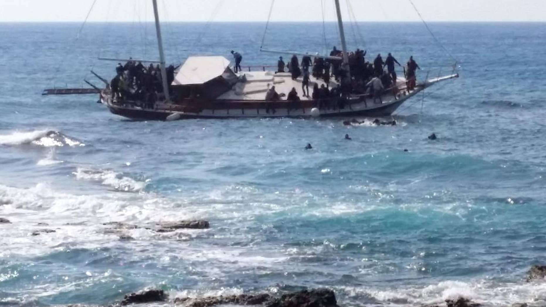 Migrants swim to reach the shore as others remainare on a listing vessel that later sunk in the eastern Aegean island of Rhodes, Greece on Monday, April 20, 2015. Greek authorities said that at least three people have died, including a child, after a wooden boat carrying tens of migrants ran aground off the  island of Rhodes. (AP Photo/Michalis Loizos) GREECE OUT