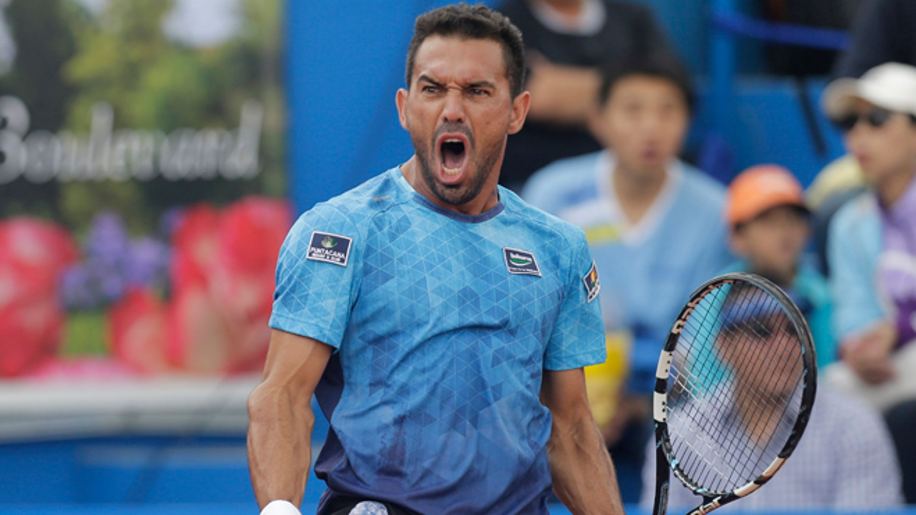 Victor Estrella from the Dominican Republic celebrates a winning a point against Spain's Feliciano Lopez in the final match of the ATP World Tour Ecuador Open Quito tournament, in Quito, Ecuador, Sunday, Feb. 8, 2015. Estrella became the oldest first-time winner of an ATP event in the Open Era, beating top-seeded Lopez. The 34-year-old Dominican won 6-2, 6-7 (5), 7-6 (5) in his first ATP final. He was the first Dominican to reach a top-level ATP final. (AP Photo/Dolores Ochoa)
