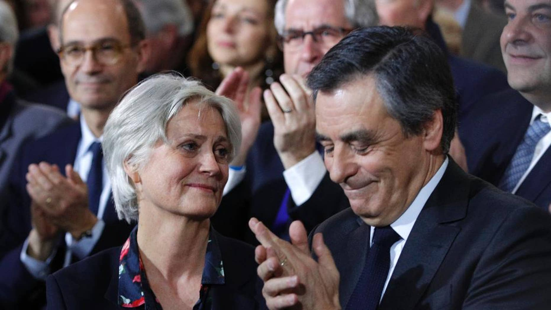 Conservative presidential candidate Francois Fillon applauds while his wife Penelope looks on as they attend a campaign meeting in Paris, Sunday, Jan. 29, 2017. Financial prosecutors are investigating an allegedly fake but handsomely paid job held by the former prime minister's wife, Penelope. (AP Photo/Christophe Ena)