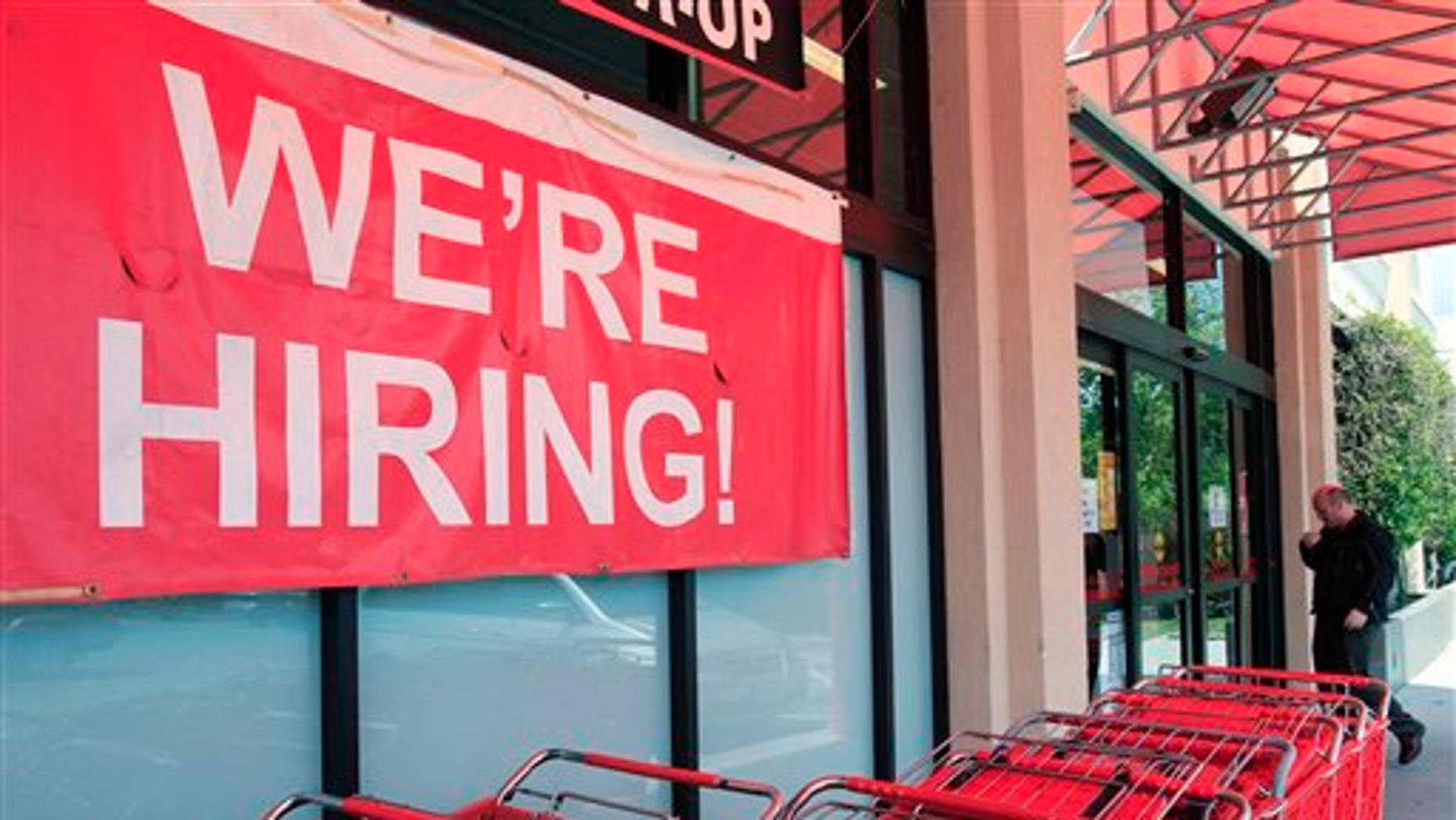 """In this April 25, 2011 photo, a """"We're Hiring!"""" sign is shown at Office Depot in Mountain View, Calif. More people sought unemployment benefits last week, the second rise in three weeks, a sign the job market's recovery is slow and uneven.(AP Photo/Paul Sakuma)"""