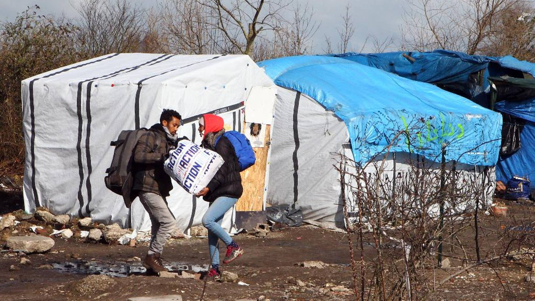 FILE - In this Thursday, March 3, 2016 file photo, unidentified migrants leave the makeshift camp near Calais, France. Residents of Champtercier fear their hamlet in the foothills of the Alps is about to become a new flashpoint for Europe's migrant crisis: Its population of 800 is slated to grow sharply when it takes in 100 migrants from an overflowing camp in Calais next month. (AP Photo/Michel Spingler, File)