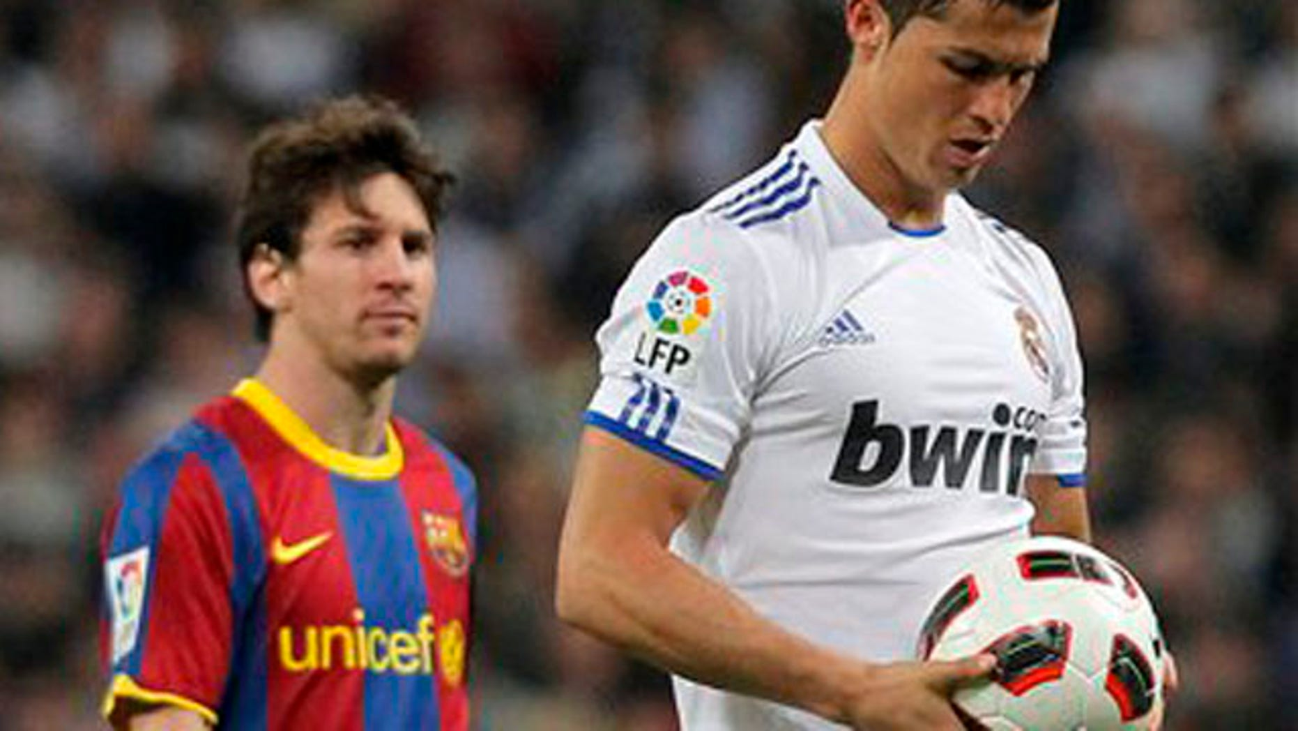 Real Madrid's  Cristiano Ronaldo from Portugal, right, holds the ball besides Barcelona's  Lionel Messi from Argentina, during their Spanish La Liga soccer match at the Santiago Bernabeu stadium in Madrid, Saturday, April 16, 2011. (AP Photo/Andres Kudacki)