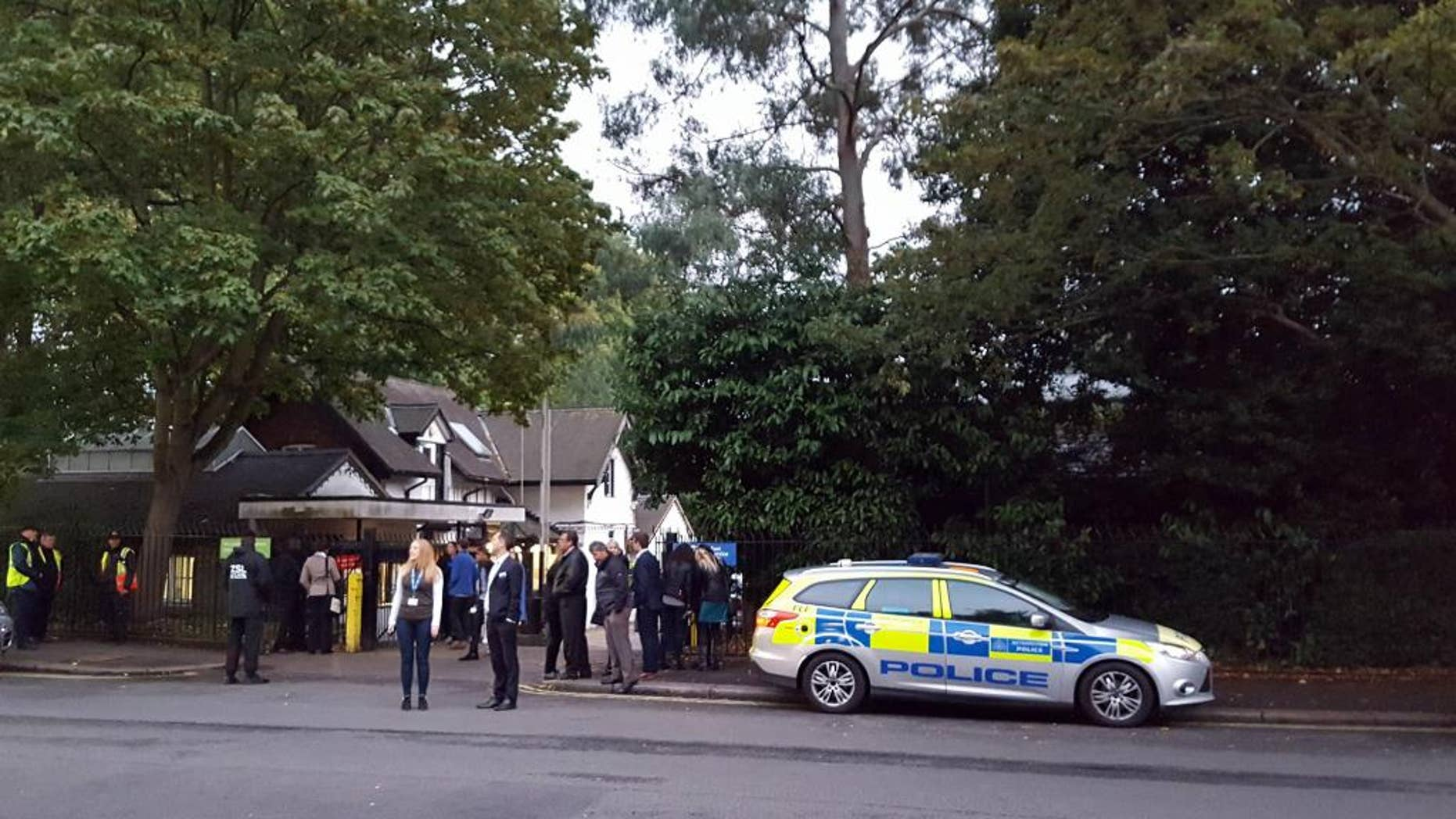 Police and evacuated visitors stand outside London Zoo after a gorilla escaped in London, Thursday, Oct. 13, 2016. London police say an incident involving a gorilla that escaped from its enclosure at the London Zoon has been concluded. There are reports the animal was subdued Thursday with a tranquilizer gun and recaptured. There were no initial reports of injuries. (Lynne Chapman via AP)